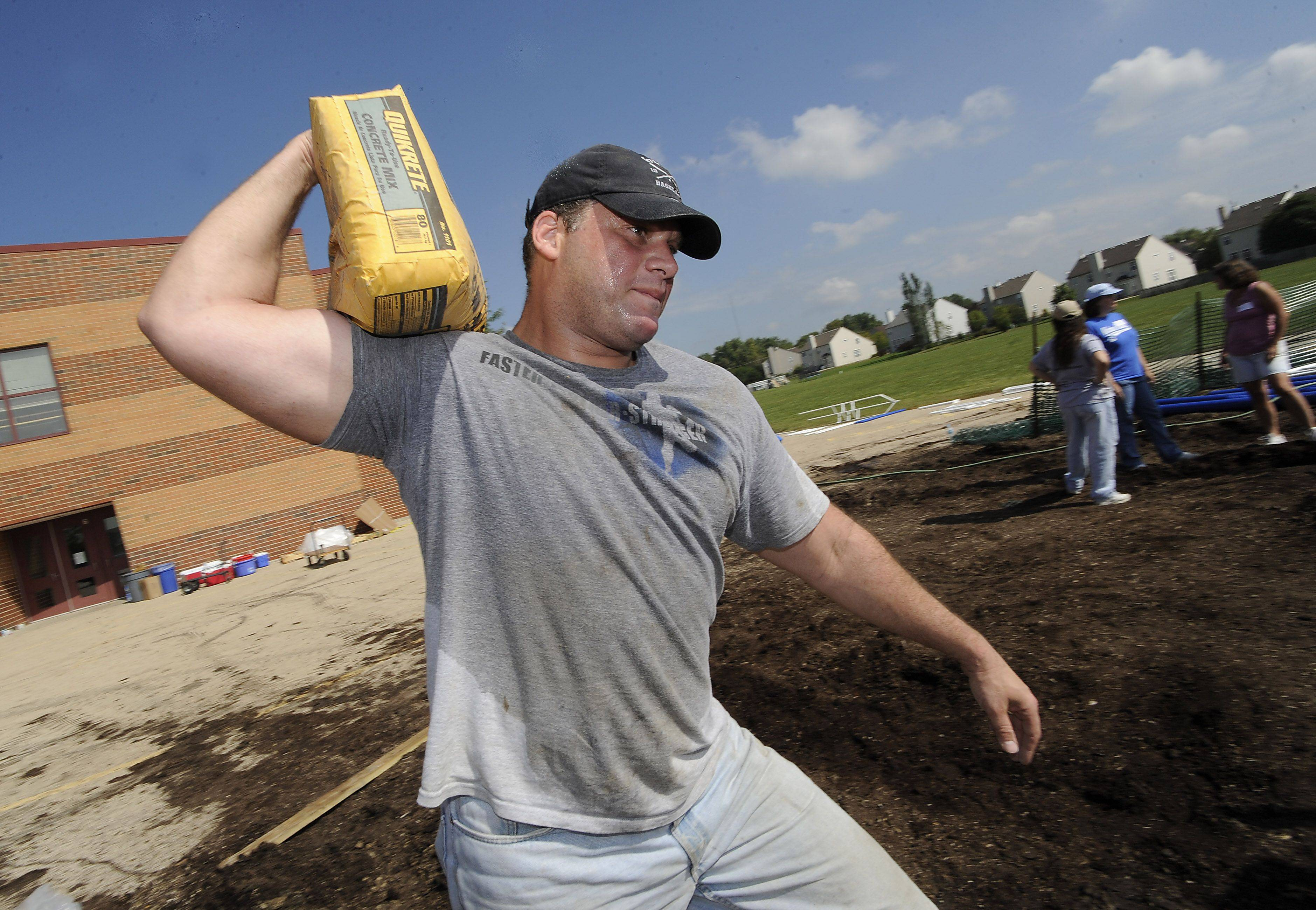 Joe Abbate of Bartlett does the heavy lifting of 80-pound bags of concrete mix as he and other parents of Nature Ridge Elementary School in Bartlett work recently to build a new playground that was PTO-funded for all the kids in the school, including students with disabilities.