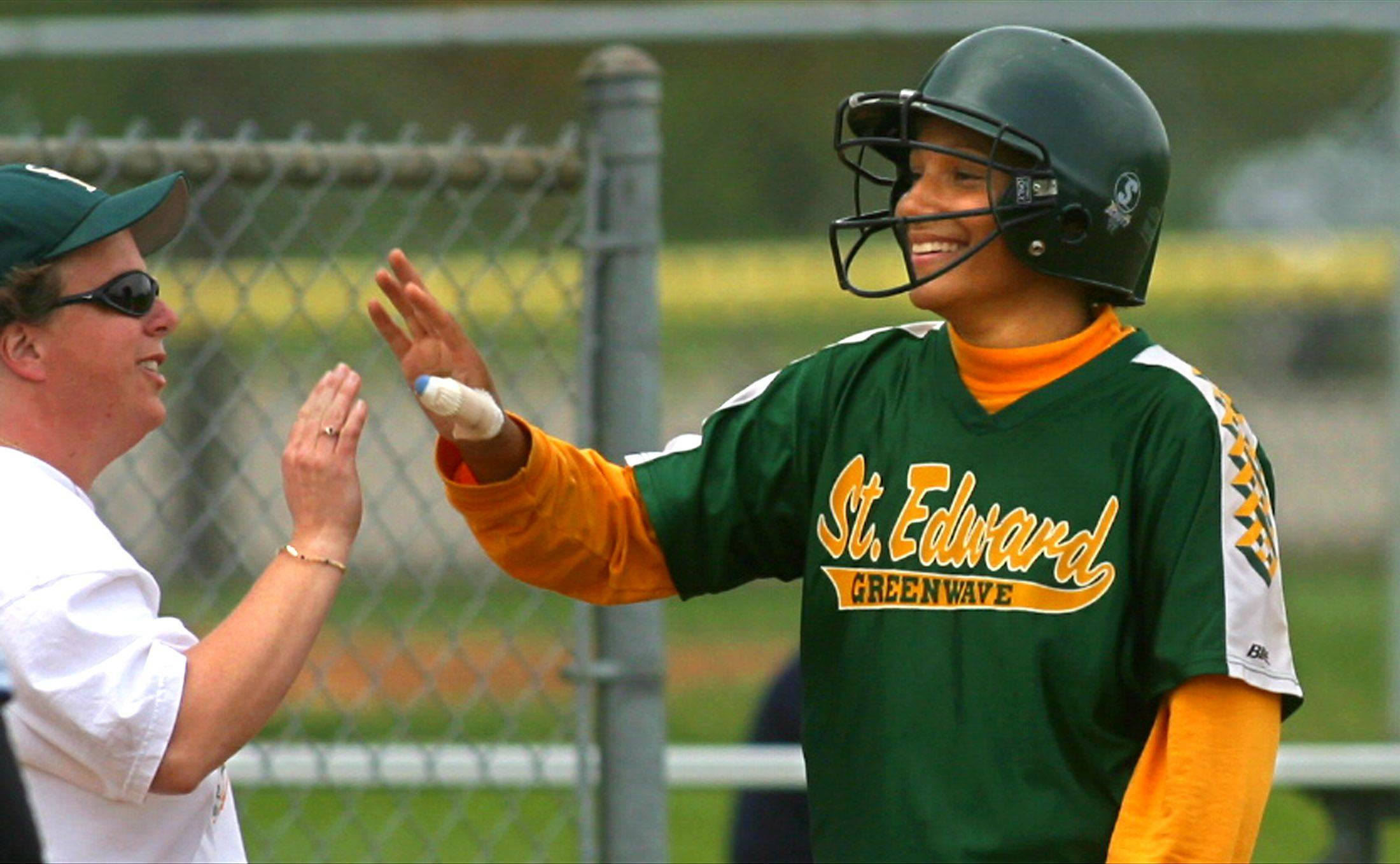 St Edward graduate Lissa Fehlman (right) is congratulated at third base by coach Peg Corcoran during the 2003 softball season. Fehlman will be inducted into the St. Edward Hall of Fame next weekend.