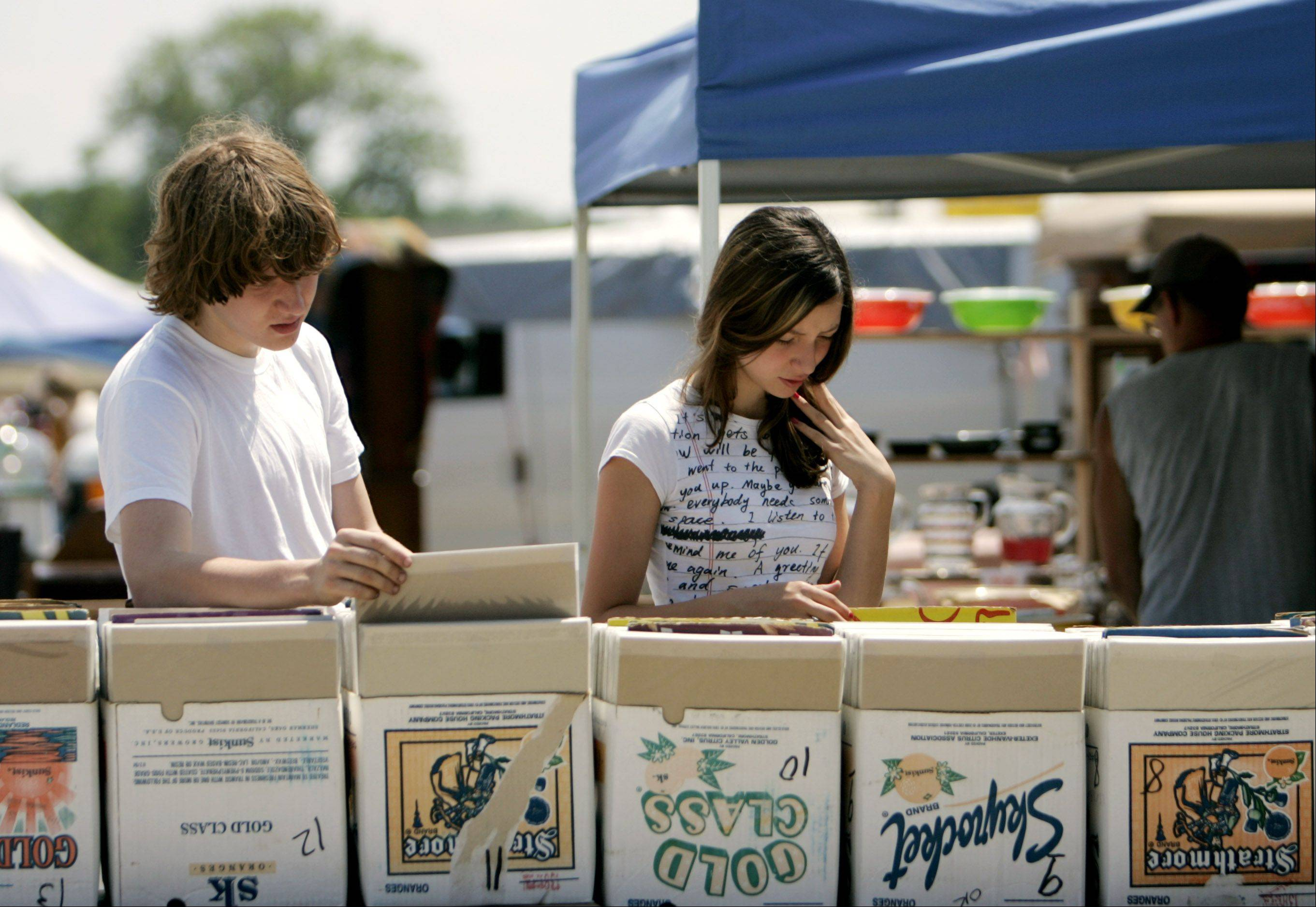 Shoppers look through old advertisements and posters at the Kane County Flea Market. Coach has sued the flea market and several vendors over the selling of counterfeit goods.