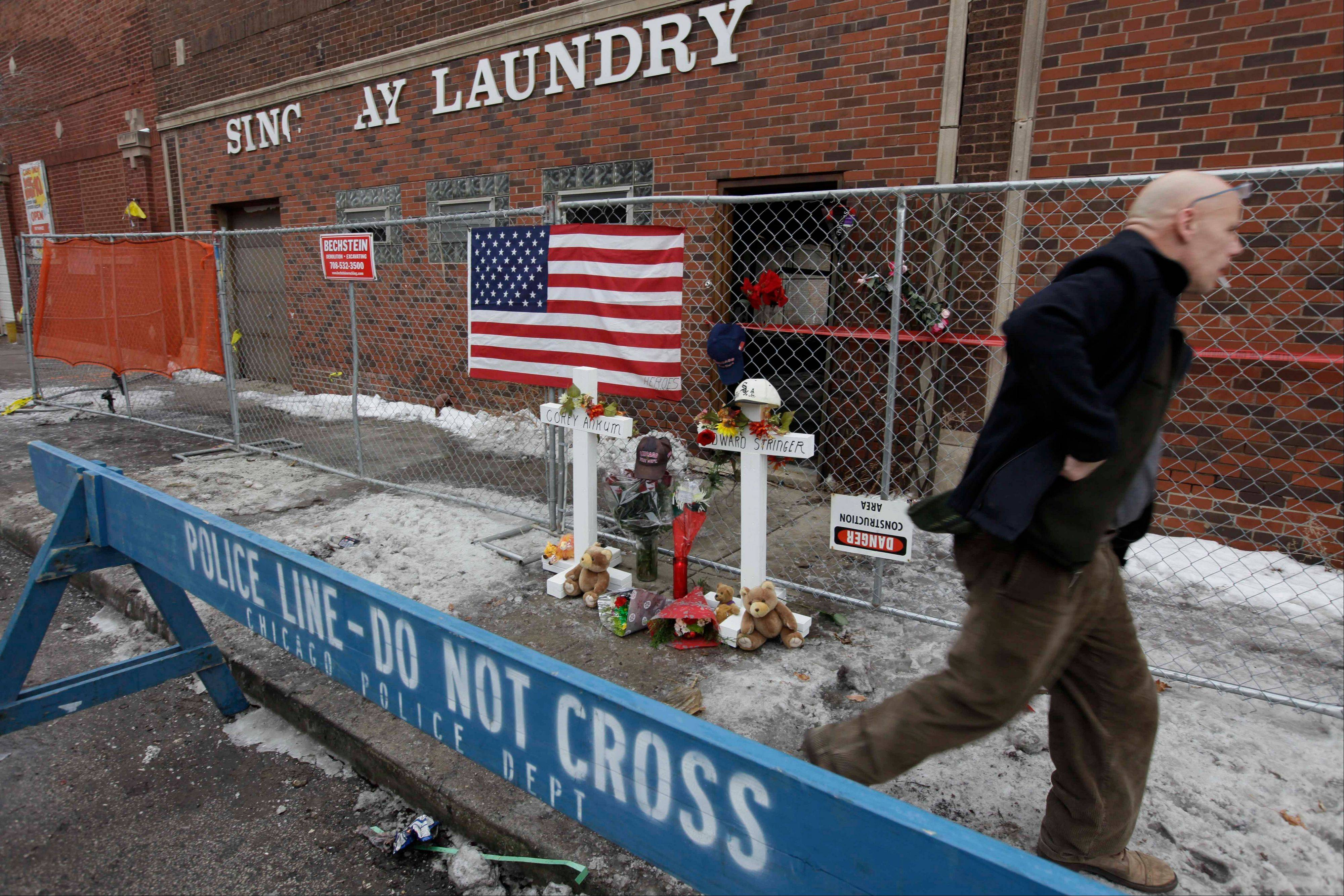 A private investigator walks past a makeshift memorial at the scene of a fire where a wall collapsed killing two and injuring more than a dozen firefighters in Chicago. A federal agency has found that poor communication and too few radios contributed to the deaths of the firefighters.