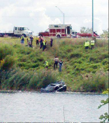 Emergency responders remove a car about 12:15 p.m. Friday from a water retention pond just north of I-88 near Winfield Road in Warrenville.