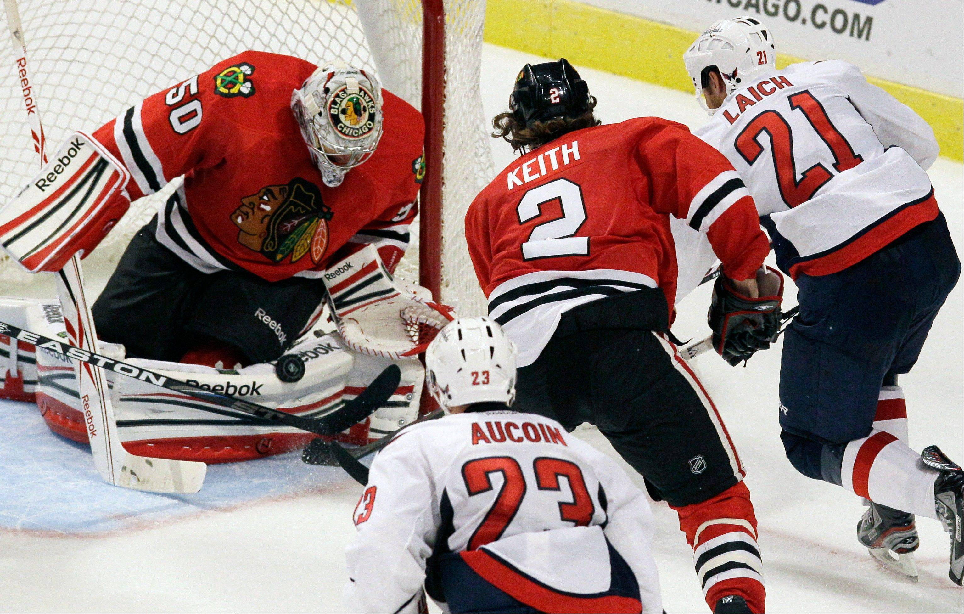 Blackhawks goalie Corey Crawford (50) saves a shot by Washington's Brooks Laich as Duncan Keith (2) looks on during the third period of the Hawks' 3-2 preseason victory Friday night at the United Center.