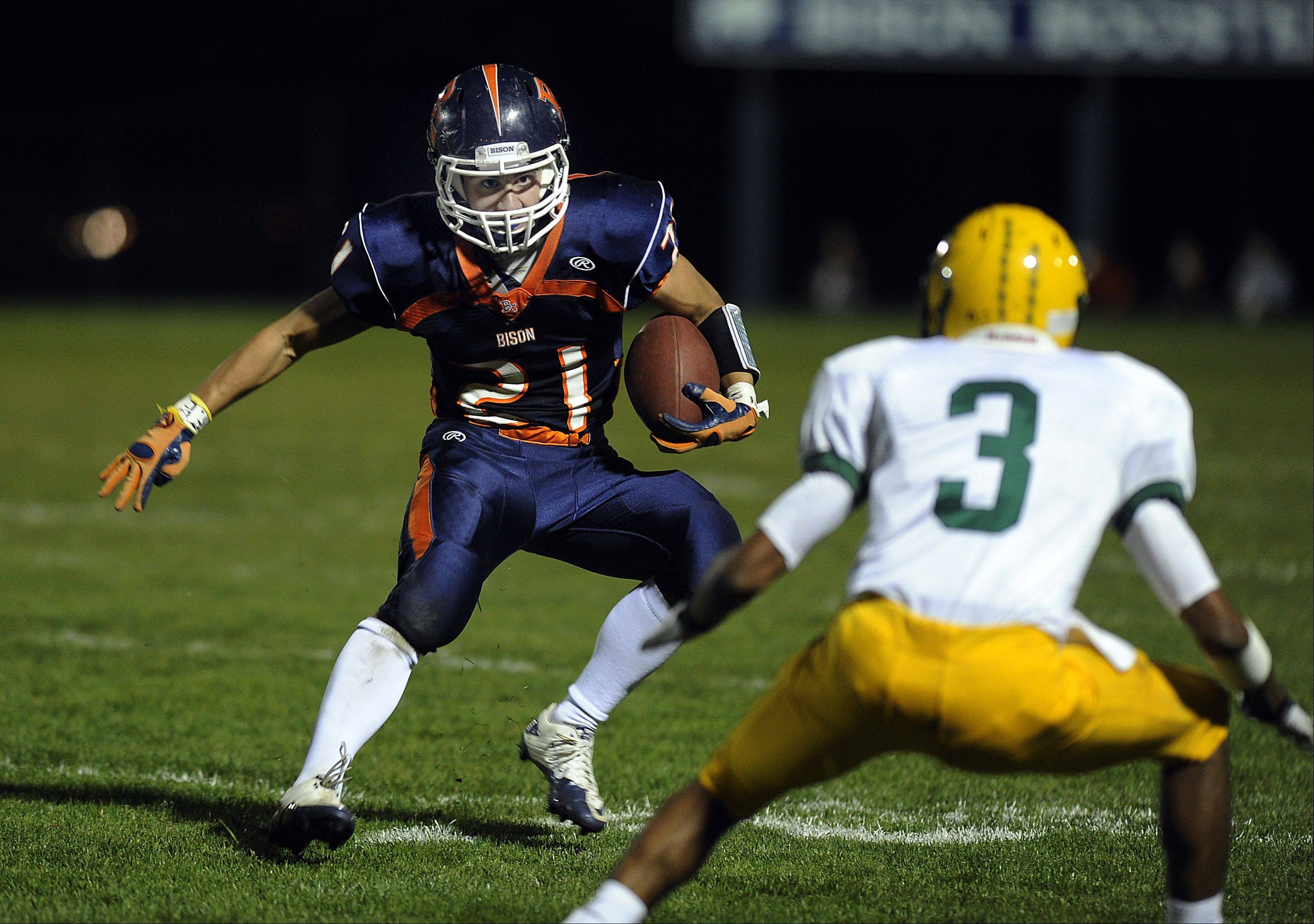 Buffalo Grove�s Alex Fritz stares down Elk Grove�s Kishan Patel as he runs for yardage slipping on the grass in the varsity matchup at Buffalo Grove High School on Friday.