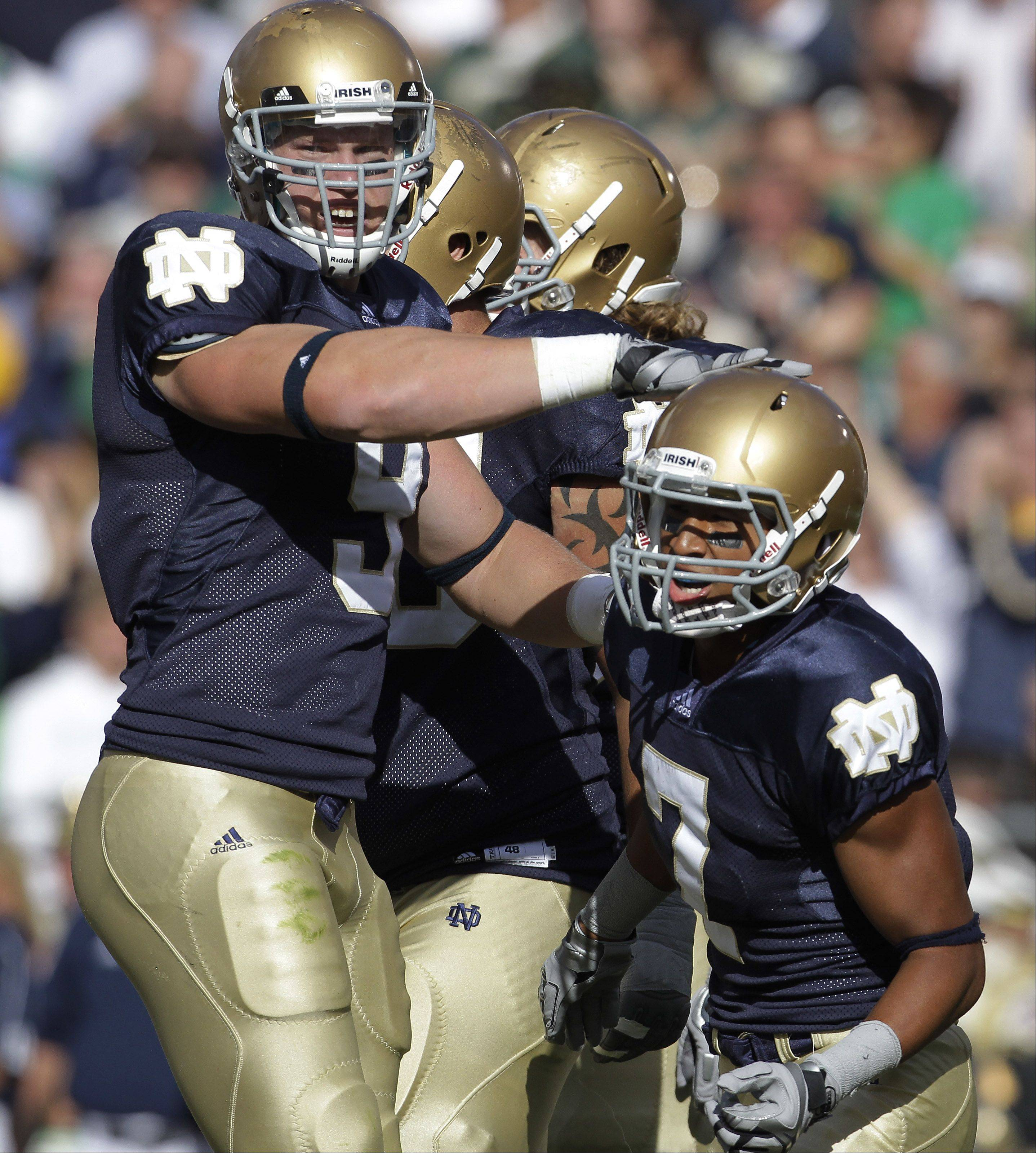 Notre Dame wide receiver TJ Jones, right, is congratulated by tight end Kyle Rudolph after Jones scored on a 5-yard touchdown reception during the third quarter of an NCAA college football game against Purdue in South Bend, Ind., Saturday, Sept. 4, 2010. (AP Photo/Darron Cummings)
