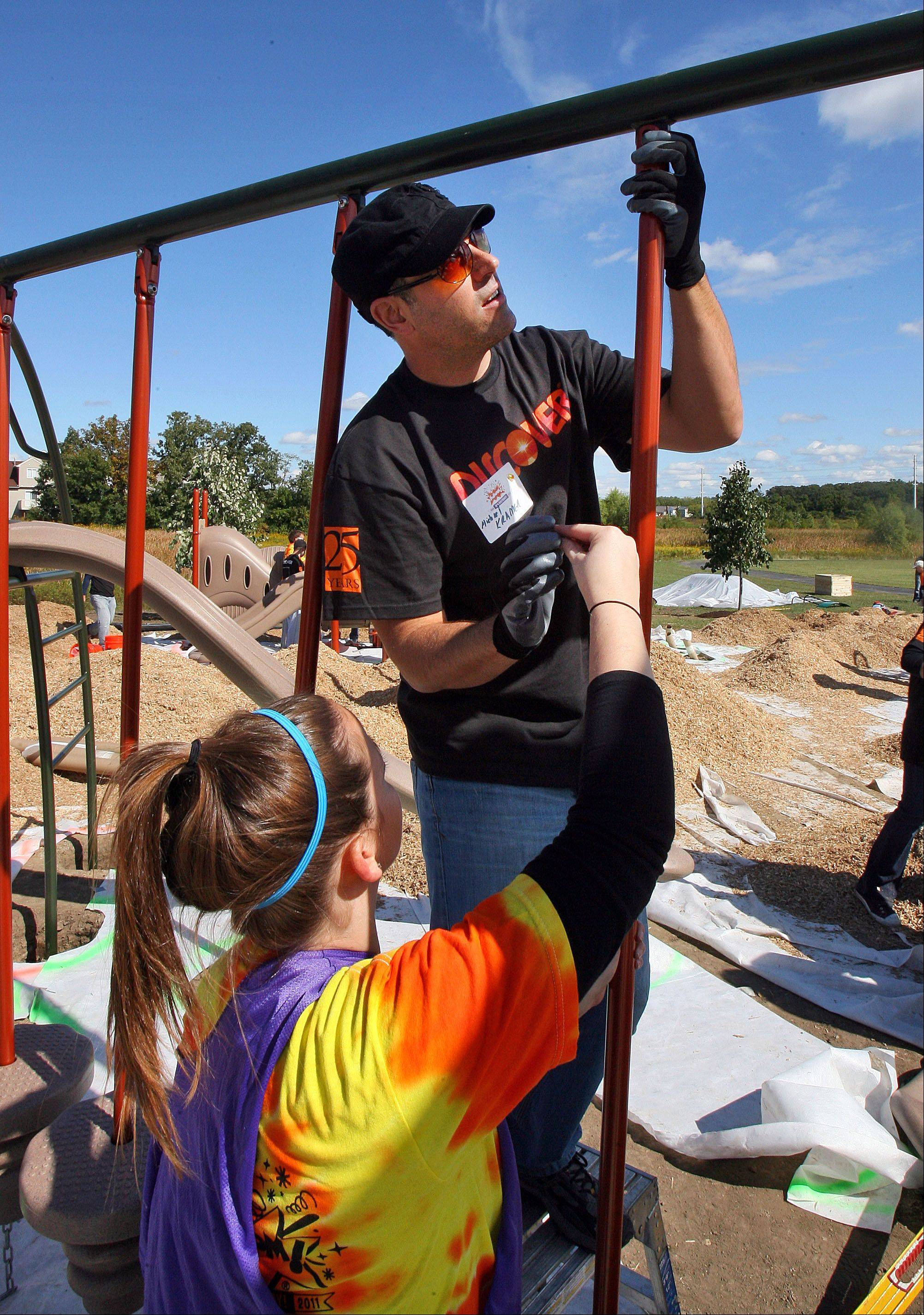 Discover employees Jessica Goodman, left, and Michael Kramer assemble a swing set Friday during a volunteer project to build a new playground at the Round Lake Sports Complex. More than 500 volunteers from Discover, the Round Lake Area Park District, Friends of the Round Lake Area Parks Foundation and KaBOOM! participated.