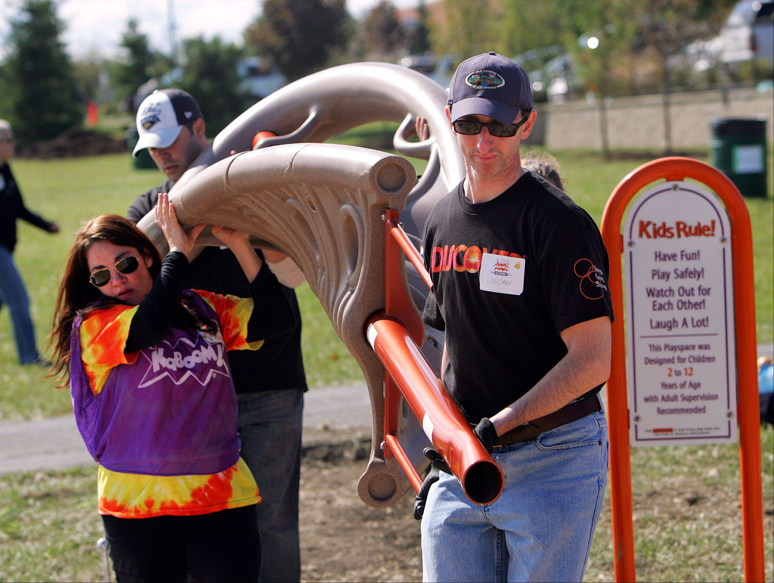 Discover employees Aimee Brohl, left, Joe Curtis, Jordan Razowsky and Angie Smith carry a piece of playground equipment Friday during construction of a new playground at the Round Lake Sports Complex. More than 500 volunteers from Discover, the Round Lake Area Park District, Friends of the Round Lake Area Parks Foundation and KaBOOM! joined forces on the project.