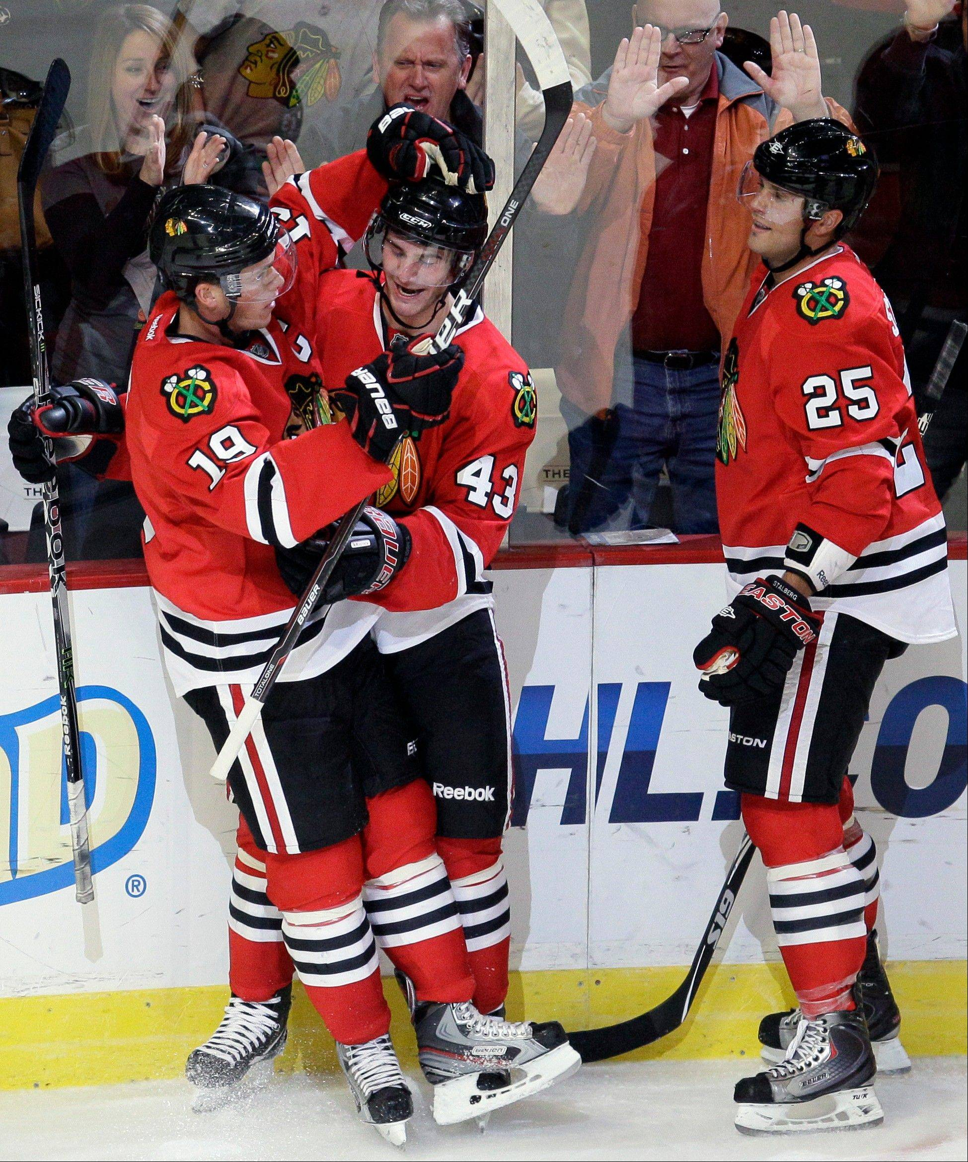 Chicago Blackhawks' Brandon Saad (43) celebrates with Jonathan Toews (19) and Viktor Stalberg (25) after Saad scoring the game winning goal during the third period of an NHL preseason hockey game against the Washington Capitals in Chicago, Friday, Sept. 23, 2011. The Blackhawks won 3-2.