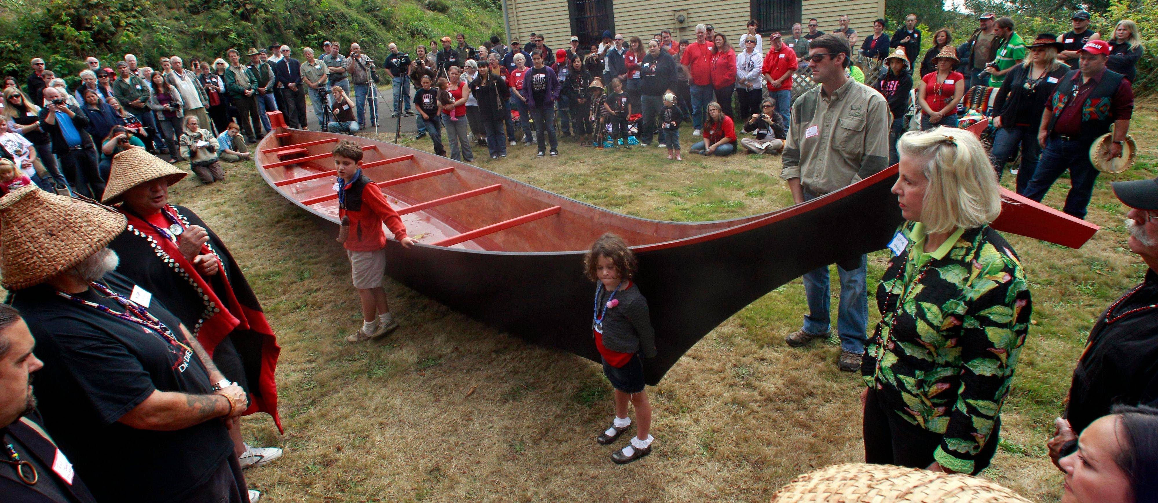 William Clark's descendants Robert Holton, 8, and his sister, Greta, 4, and their father Rob Holton and their grandmother Carlota 'Lotsie' Holton, stand in front of their gift, a 36-foot canoe as Chinook elders, left, look on Saturday during the canoe reparation ceremony.