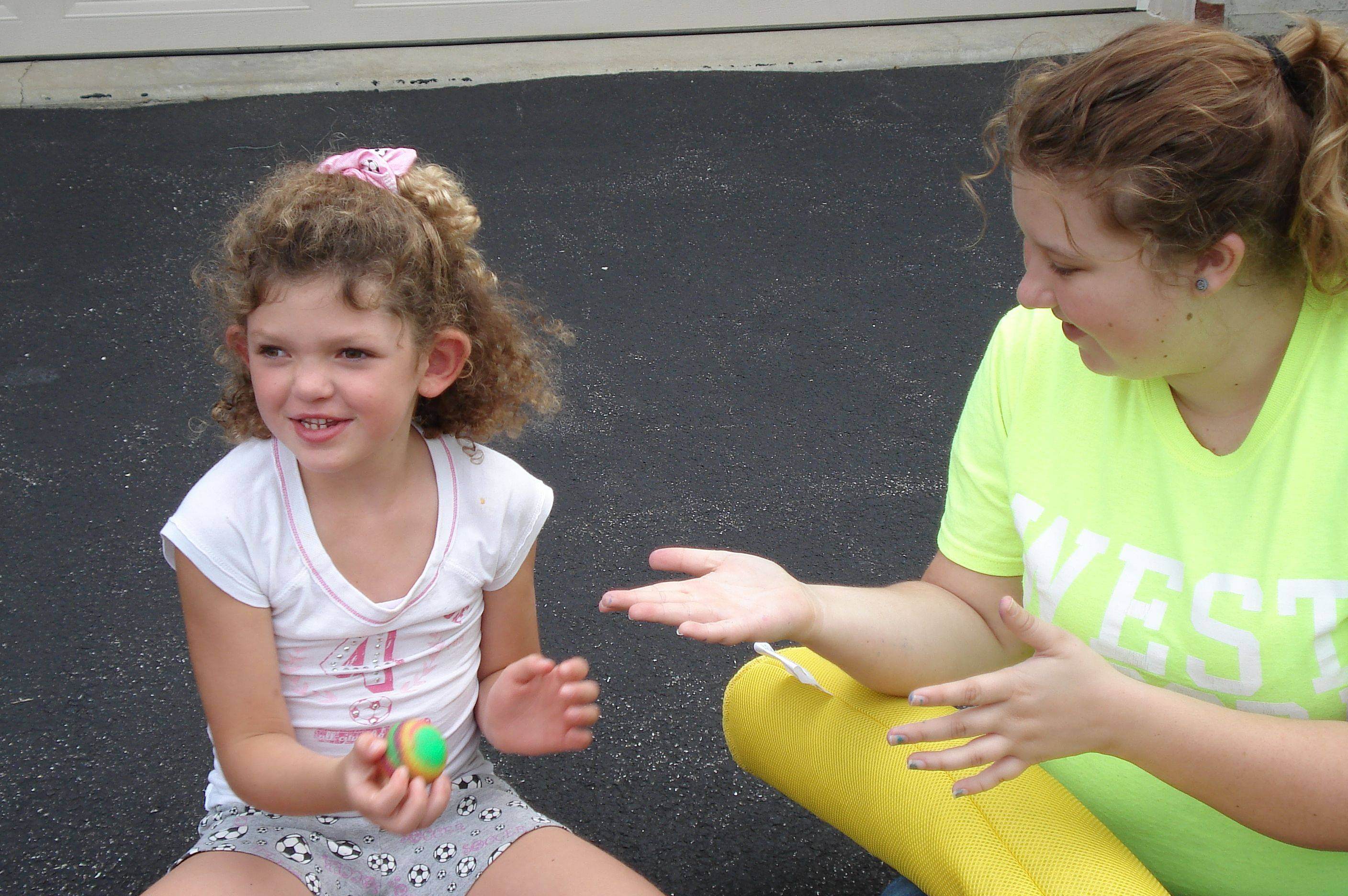 Adult volunteer Allison Greiner encourages Haley Olson to look at her when throwing a ball during a Haley's Playground class at the North Aurora Community Center. Looking at the person you are playing with is a difficult task for children with autism, playground founder Jackie Olson said. (Photo submitted by Haley's Playground Inc.)