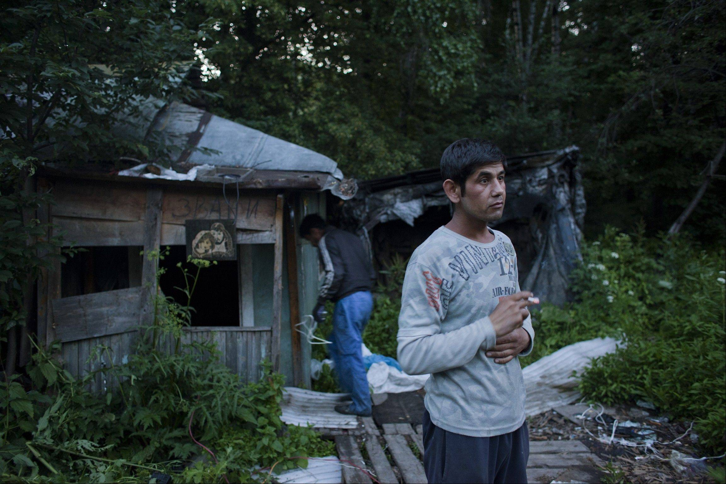Odil Sattorov, 29, takes a cigarette break outside the shack in the woods of suburban Moscow where he and two other migrants from the Khatlon region of Tajikistan live. In Moscow, prejudice against Central Asians gives young nationalists a target for their anger.
