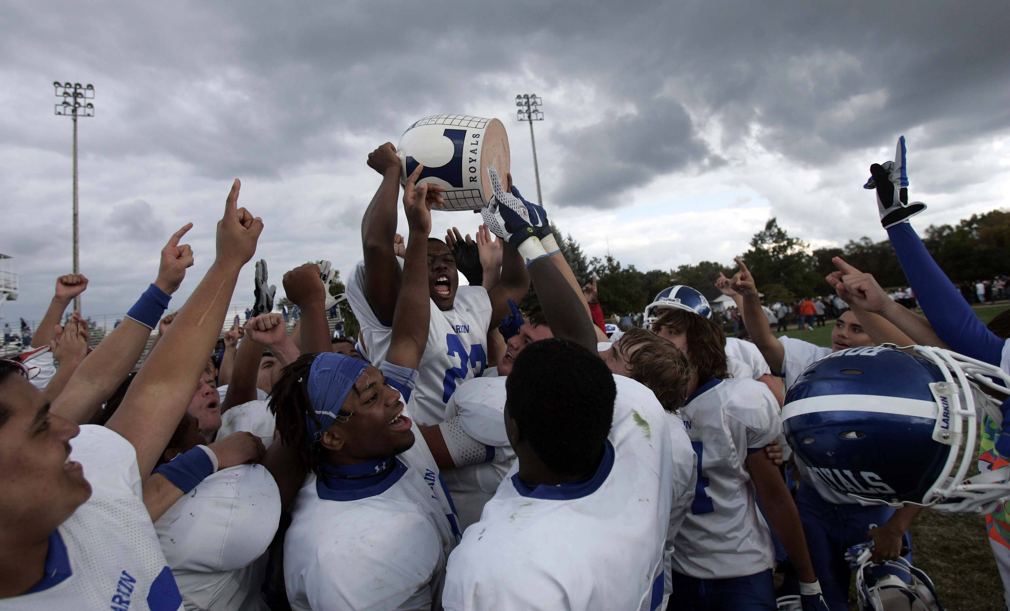 Larkin linebacker Sylvester Smith (22) hoists the Town Jug after the Royal?s victory. Larkin beat Elgin 22 to 21 to win the town jug during the cross town football game Saturday, September 24, 2011 at Memorial Field in Elgin.
