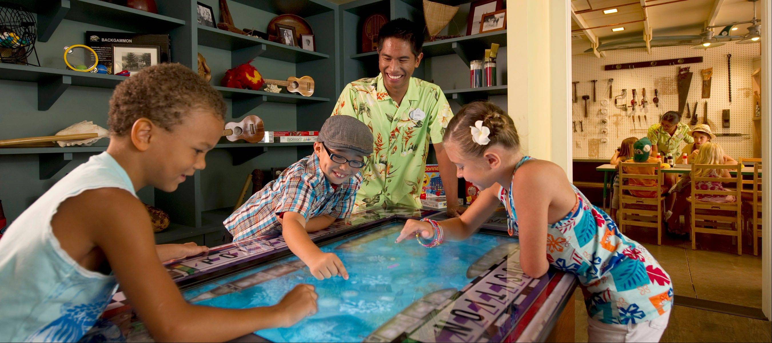 Kids play with a touch-screen game in Aunty's Beach House at Aulani, a new Disney Resort & Spa in Hawaii.