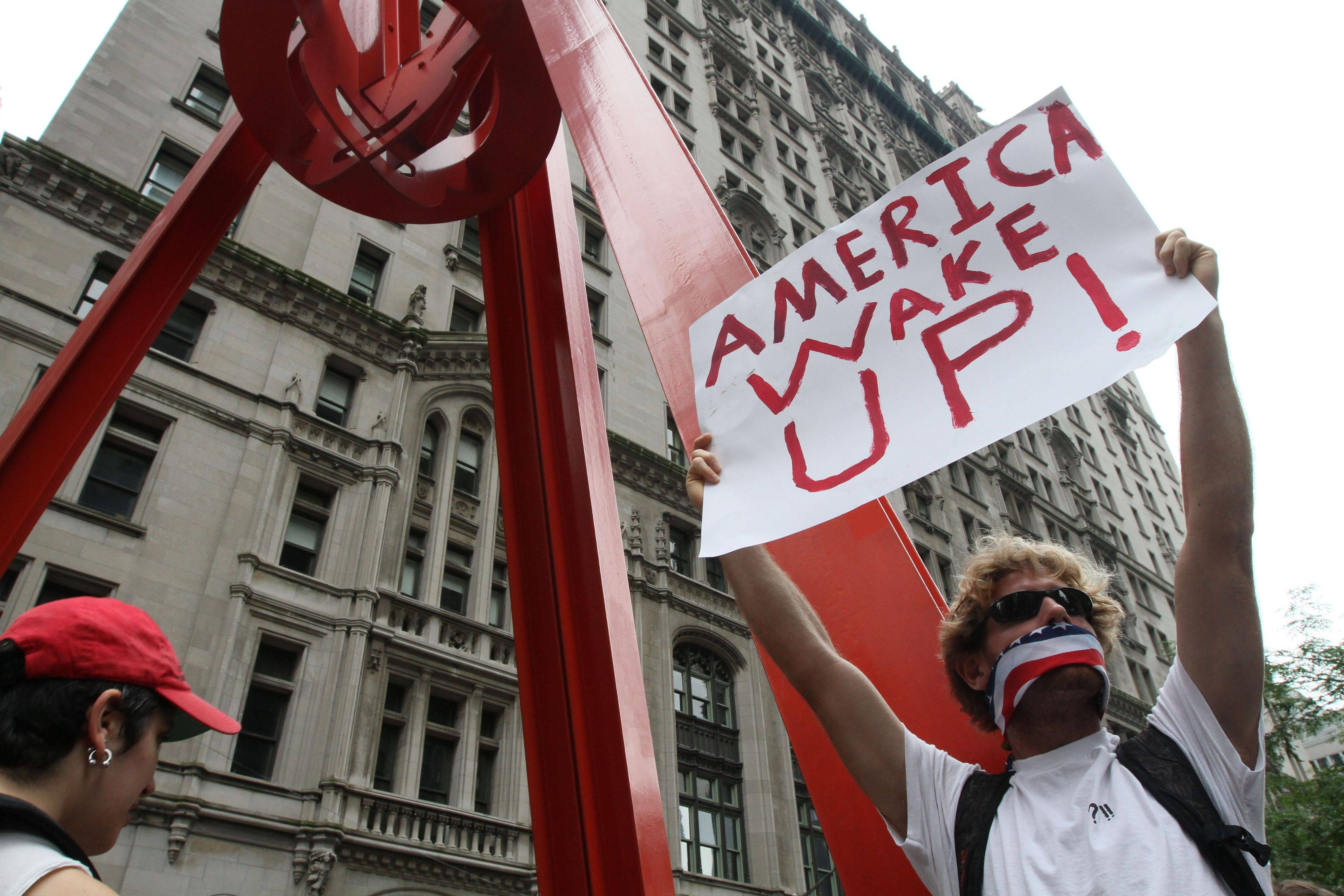 A participant in a march organized by Occupy Wall Street holds up a sign Saturday in New York. Marchers represented various causes both political and economic.