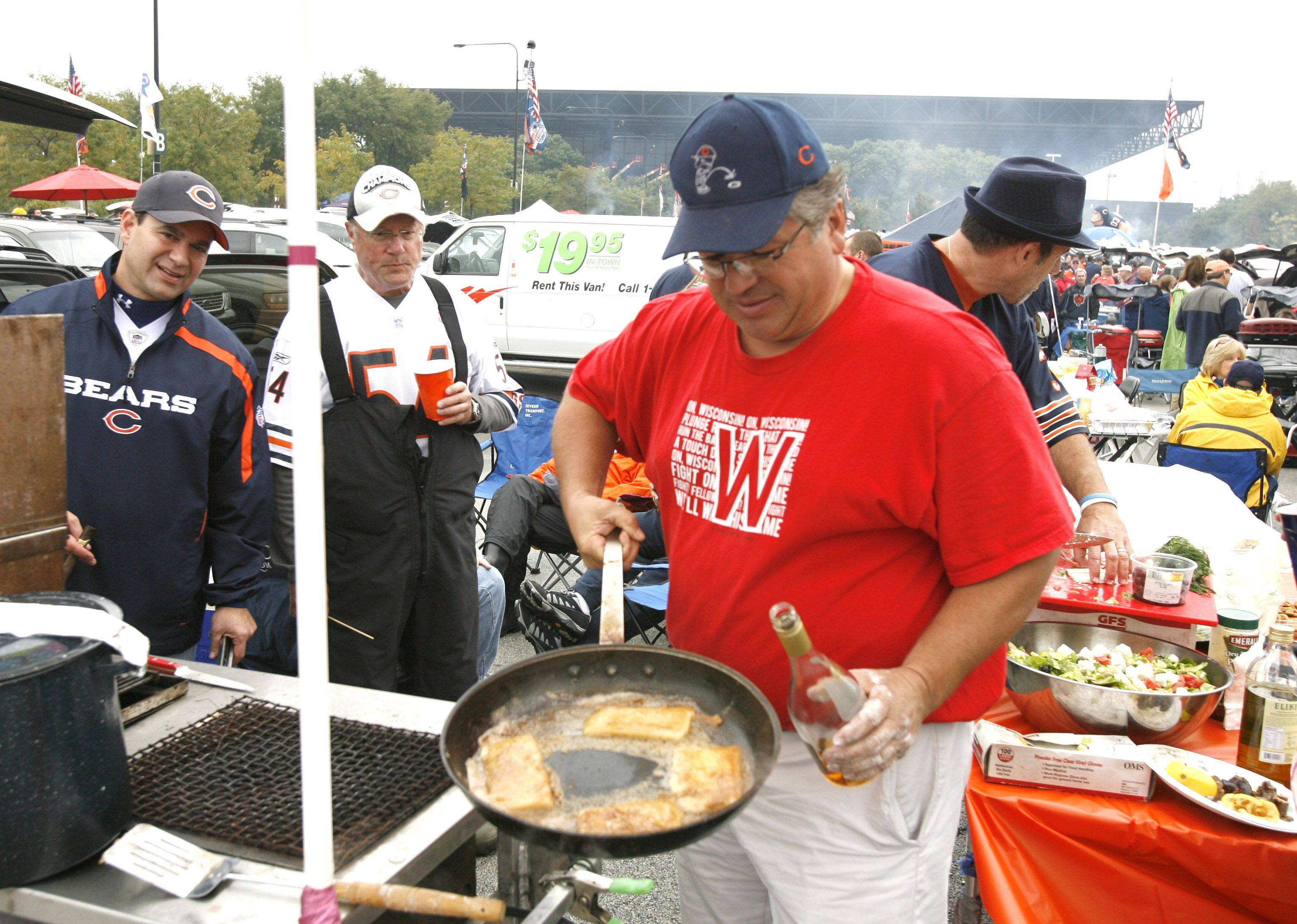 Pete Stamos of Palos Heights cooks flaming cheese during Chicago Bears and Green Bay Packers pregame tailgate.