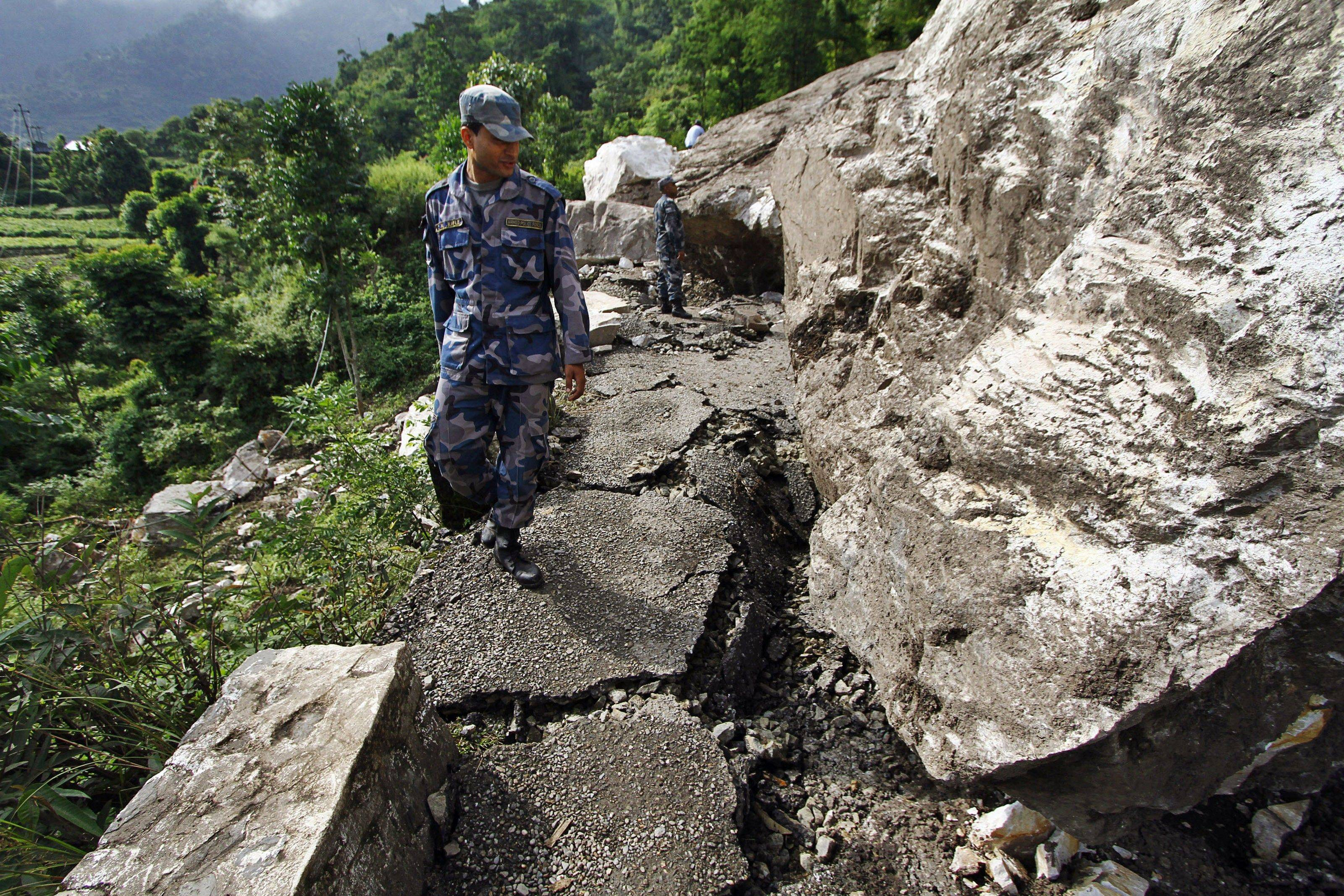 Nepalese police personnel pass by the damaged portion of the Dharan-Dhankuta road about 133 miles from Katmandu, Nepal, on Wednesday. A plane carrying tourists to view Mount Everest crashed Sunday while attempting to land in dense fog in Nepal.