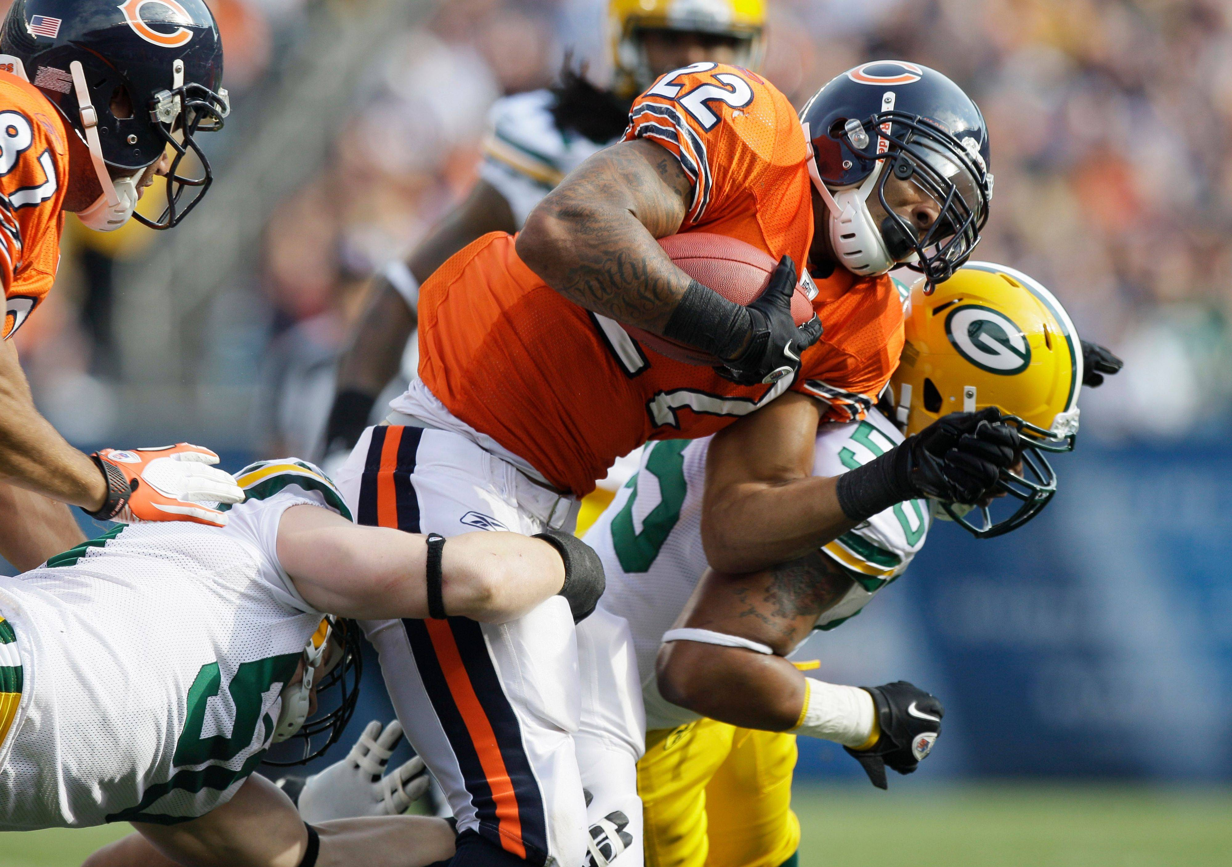 Bears running back Matt Forte is tackled by Packers linebackers A.J. Hawk, left, and Desmond Bishop in the first half Sunday.
