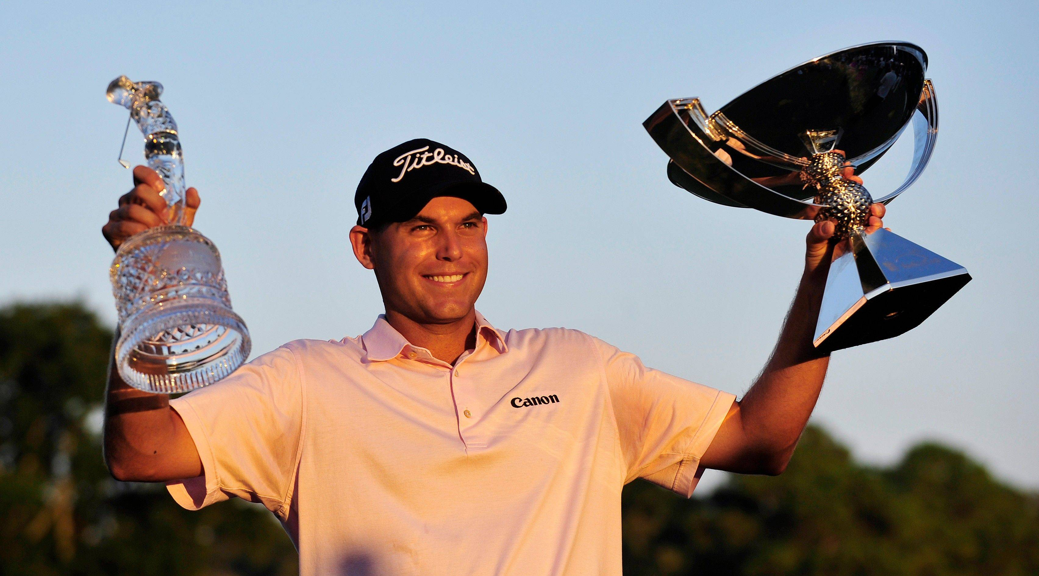 Bill Haas holds the FedEx Cup and the Tour Championship trophy after defeating Hunter Mahan in three playoff holes at East Lake Golf Club in Atlanta on Sunday.