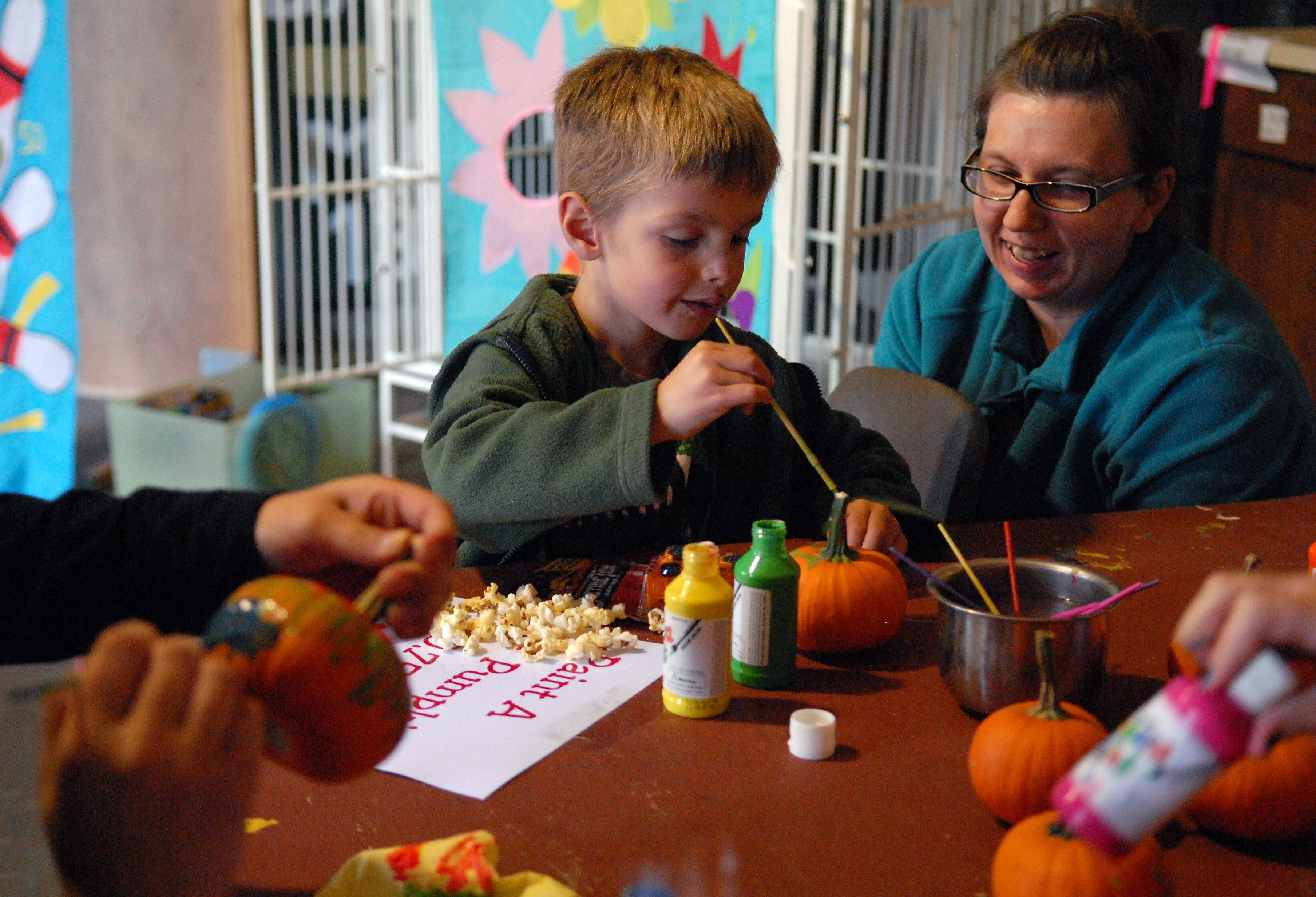 Cameron Worley, 5, of Leland, and Tabatha Ellberg, of Aurora, paint pumpkins during an open house Sunday at the Fox Valley Wildlife Center in Elburn. The open house included a bake sale, games for kids, a pie walk, and education ambassador animals which served as living learning tools.