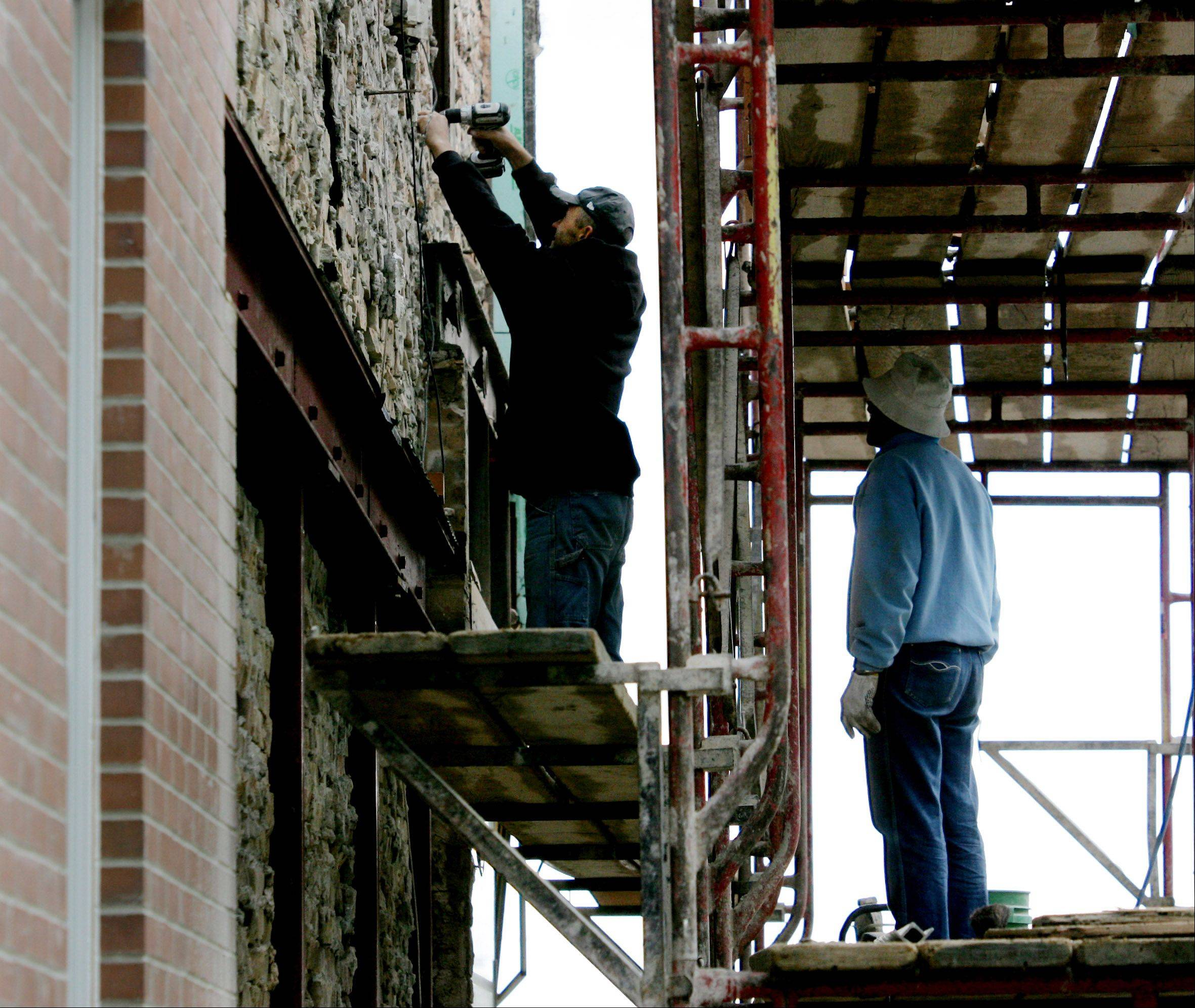 Peter Rafacz, left, and Adam Rafacz, both of R.P. Masonry, work on the brick facade Monday on the exterior of the Picnic Basket restaurant in downtown Libertyville.