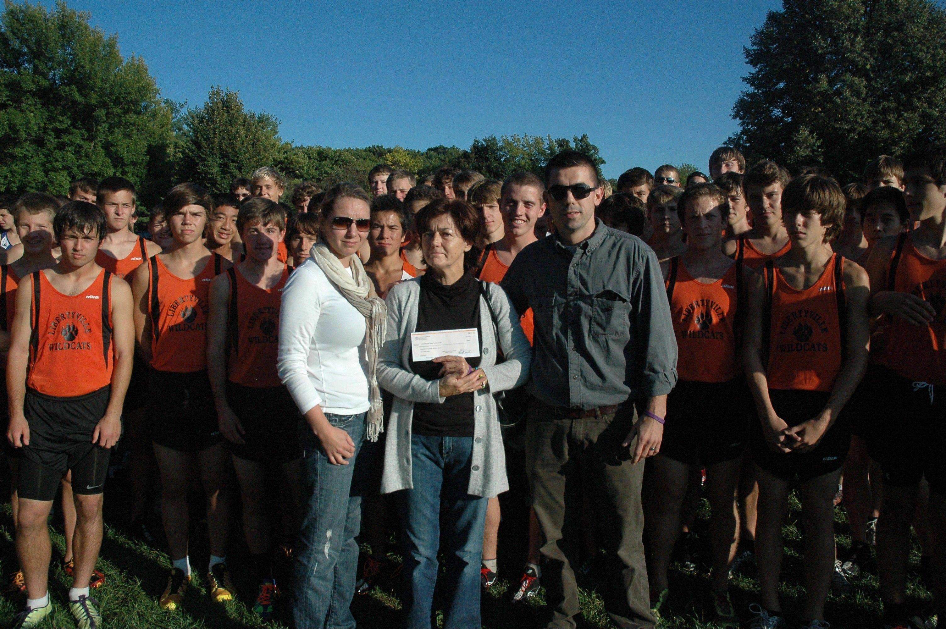 The Libertyville boys cross country team presents a check to the Drozdz family at the Lake Zurich vs. Libertyville cross country dual meet at Lakewood Forest Preserve on Sept. 19.