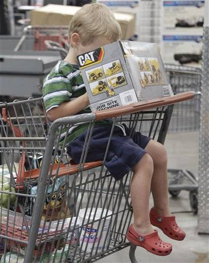 A young shopper peers into a box containing a CAT motorized job site machine, as he waits to get through the check-out at Costco in Mountain View, Calif.