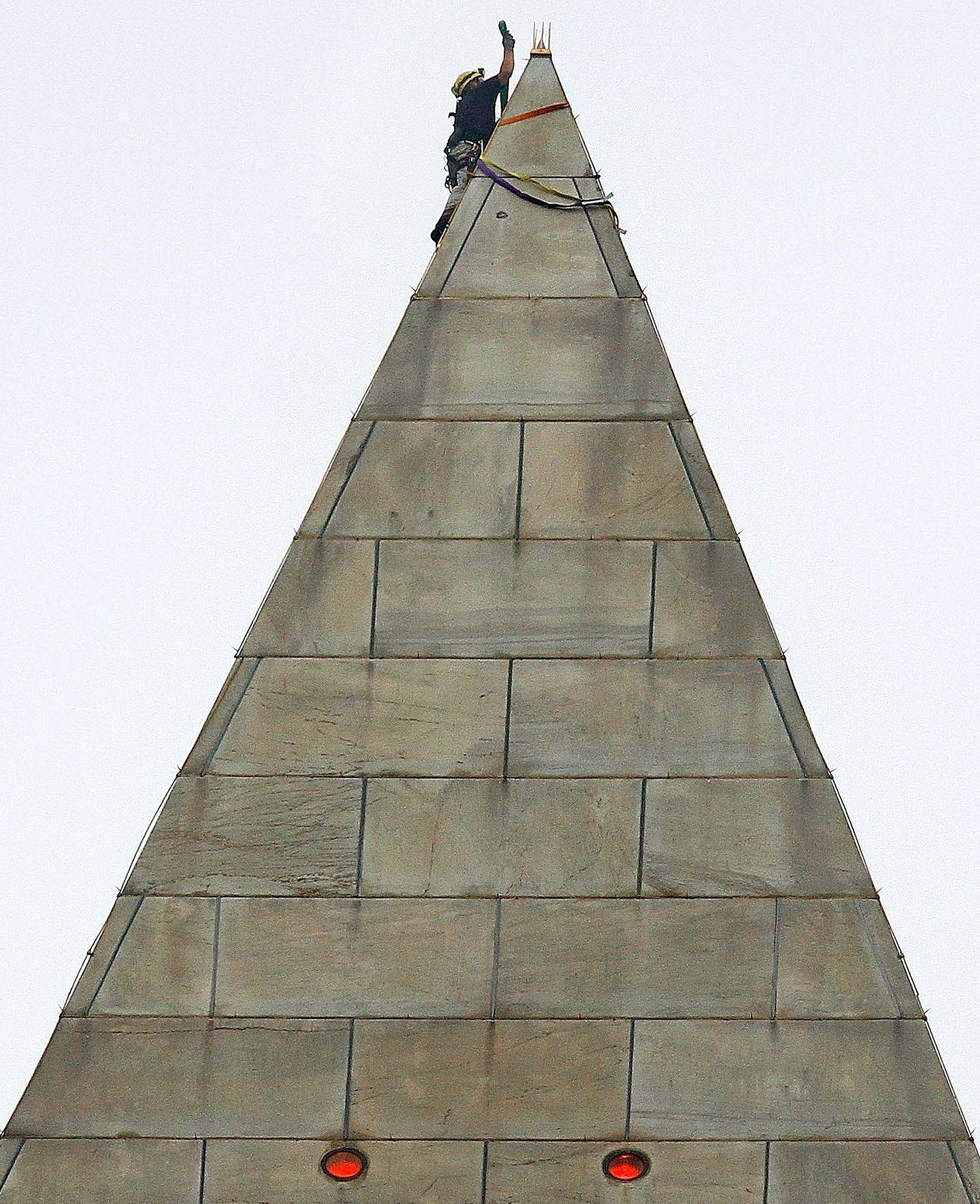 Rigging is attached to the top of the Washington Monument so engineers can rappel down the sides to survey quake damage.
