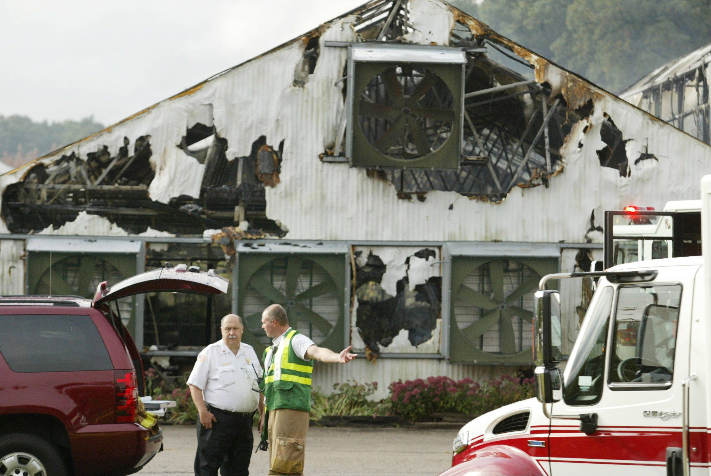 Fire officials work the scene of a fire Tuesday morning at Klehm Growers nursery in Hampshire. A large greenhouse was severely damaged.