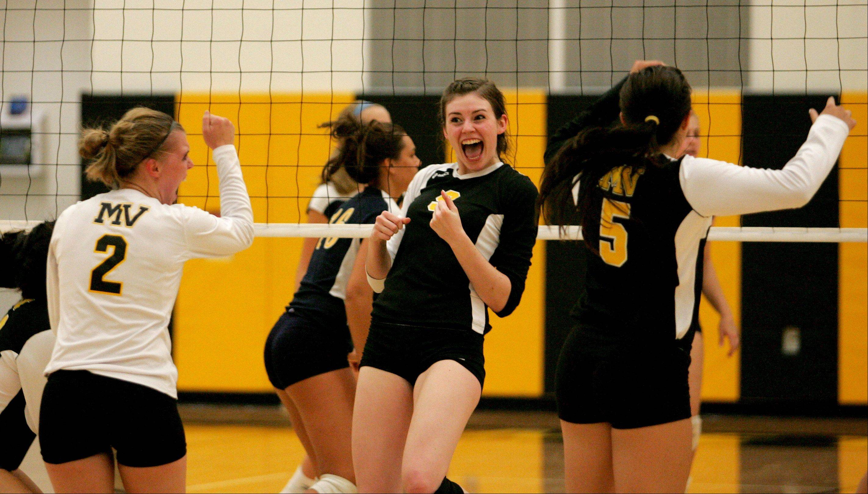 Metea Valley's Alyssa Ensminger, left, and Jessica Boddy celebrate a point won against Neuqua Valley during girls volleyball action Tuesday in Aurora.