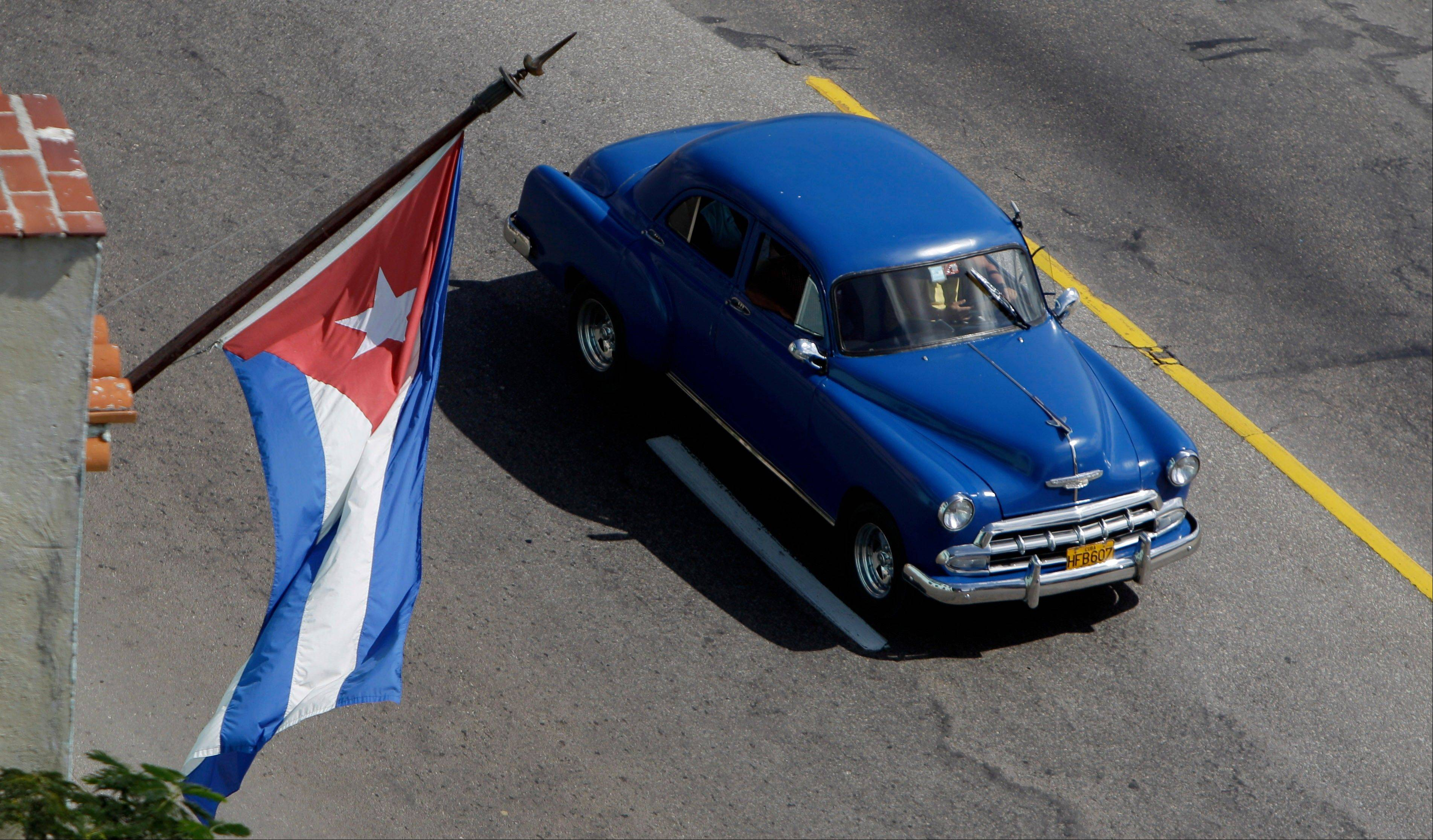 An American classic car drives past a government office flying Cuba�s national flag in Havana, Cuba, Wednesday. Cuba legalized the sale and purchase of automobiles for all citizens on Wednesday, another major step in the communist run island�s economic transformation. The 40-page Official Gazette that published the law which takes effect Oct. 1 also says that Cubans who leave the island for good can transfer ownership of their car to a relative or sell it outright. Previously, the state could seize the automobiles of those who emigrated.