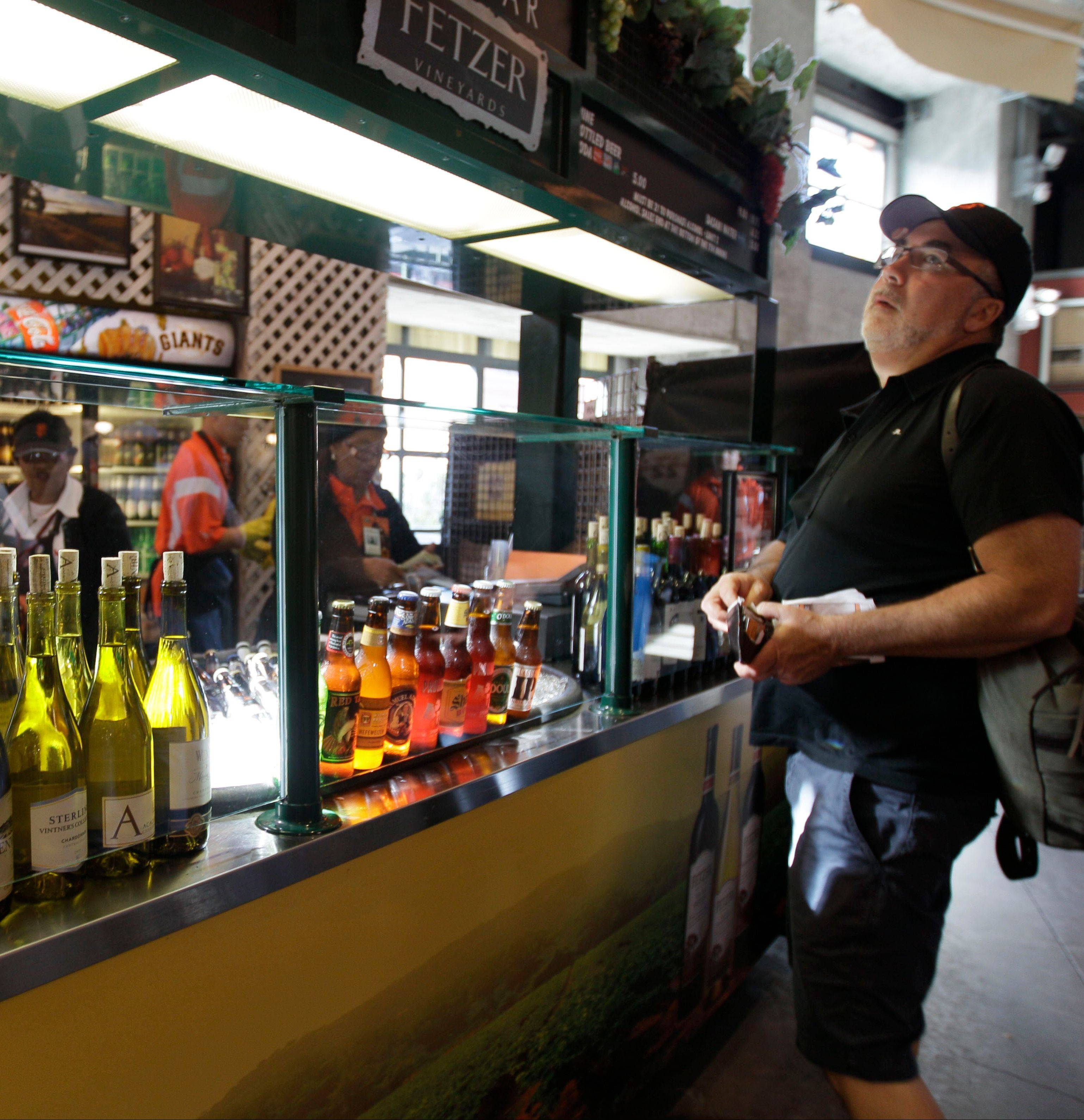 A fan looks over the menu at a wine bar at AT&T Park before the San Francisco Giants baseball game earlier this season. As the World Series approaches, fans of the grape and the great American pastime have more choices at ballparks.