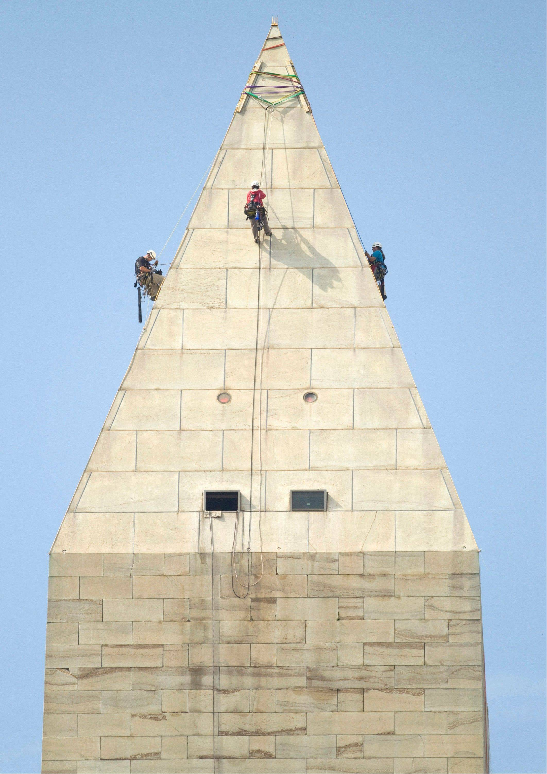 A team of engineers, from left, Dan Gach, Emma Cardini and Katie Francis, harnessed to ropes, inspect the exterior of the Washington Monument for damage caused by last month�s earthquake on Wednesday.