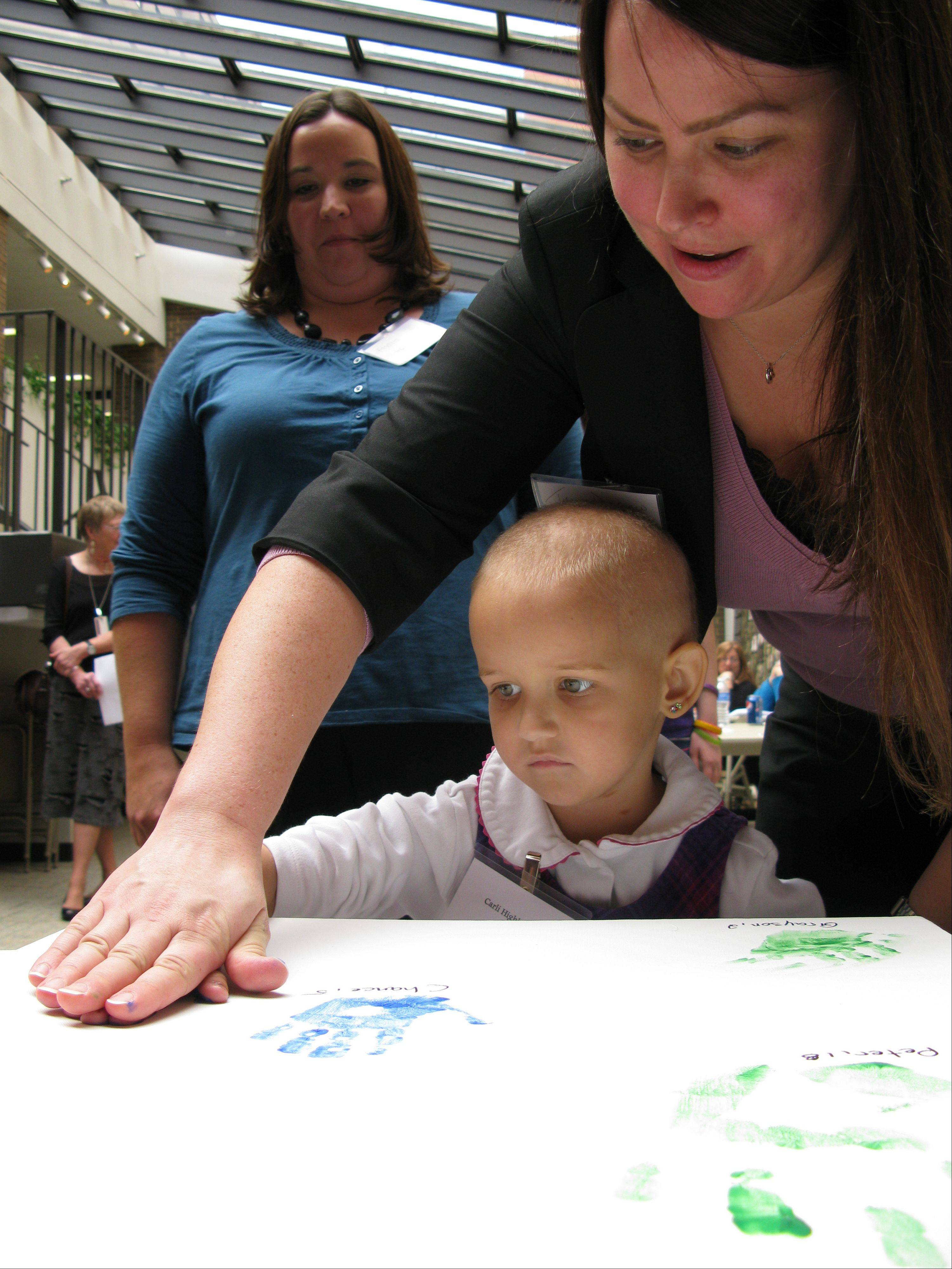 Hyundai employee Tricia Dunfield helps 4-year-old Carli Highberger of Lombard make a hand imprint on canvas while Carli's mother, Andrea, watches. Carli is being treated at Advocate Lutheran General Children's Hospital in Park Ridge.