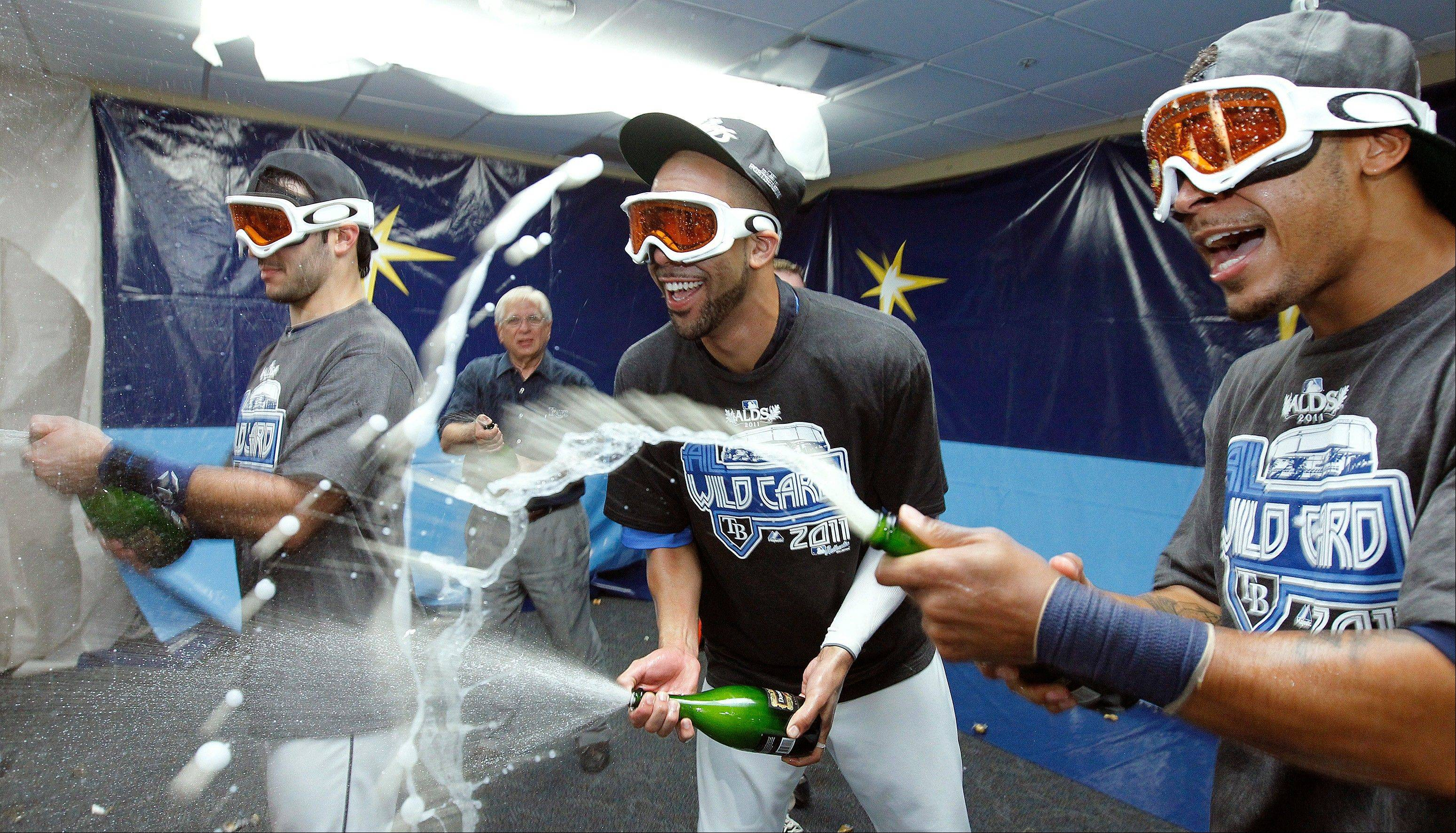 Tampa Bay Rays, from left, Sean Rodriguez, David Price, and Desmond Jennings spray champagne as they celebrate early Thursday after the Rays clinched the AL wild card with an 8-7 win over the New York Yankees.