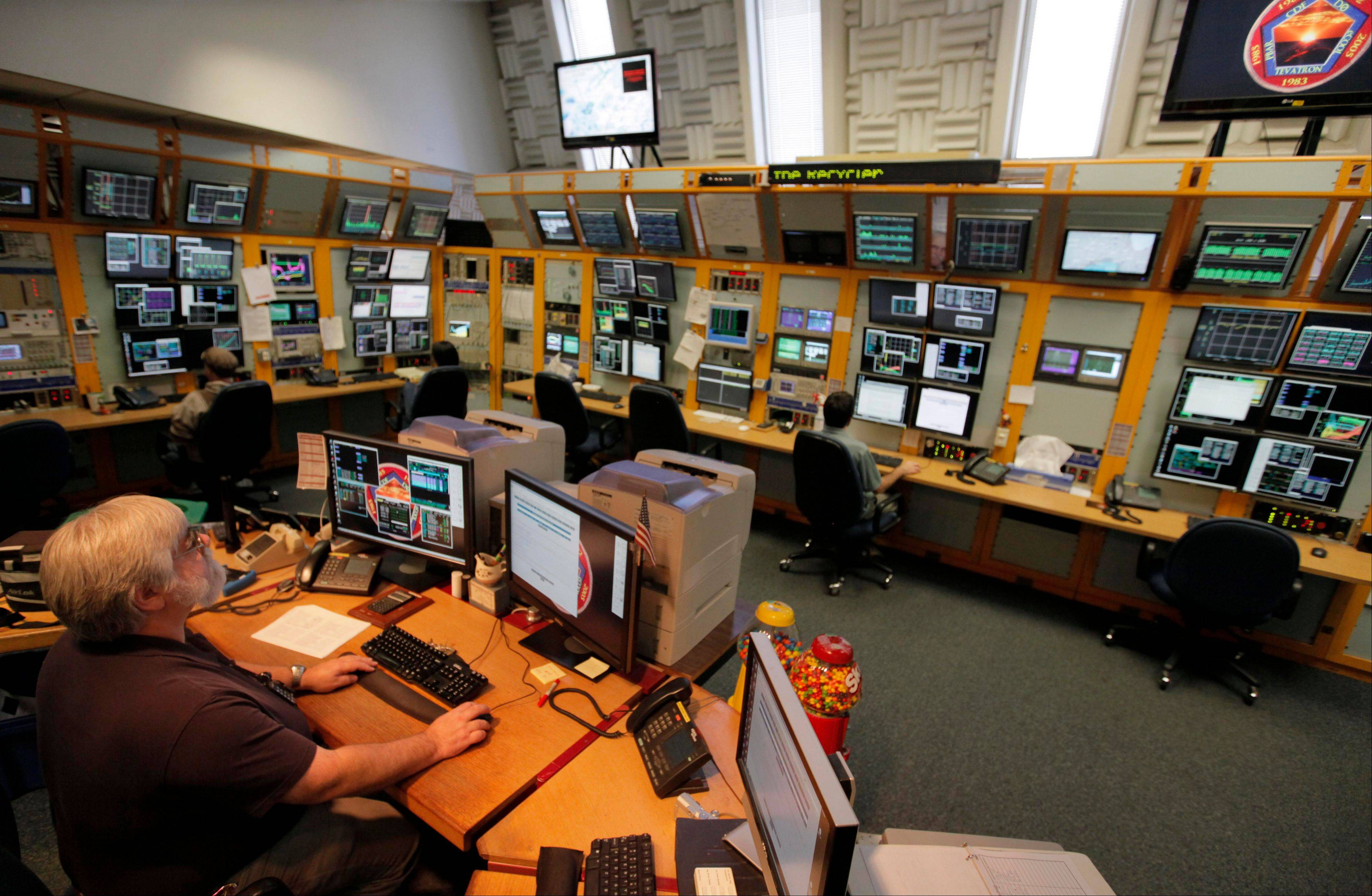 Employees man the main control room that runs all the accelerators at the Fermi National Accelerator Laboratory in Batavia, including the Tevatron collider. On Friday, physicists will shut down the Tevatron, a once-unrivaled atom smasher that has been eclipsed by the Large Hadron Collider in Europe.