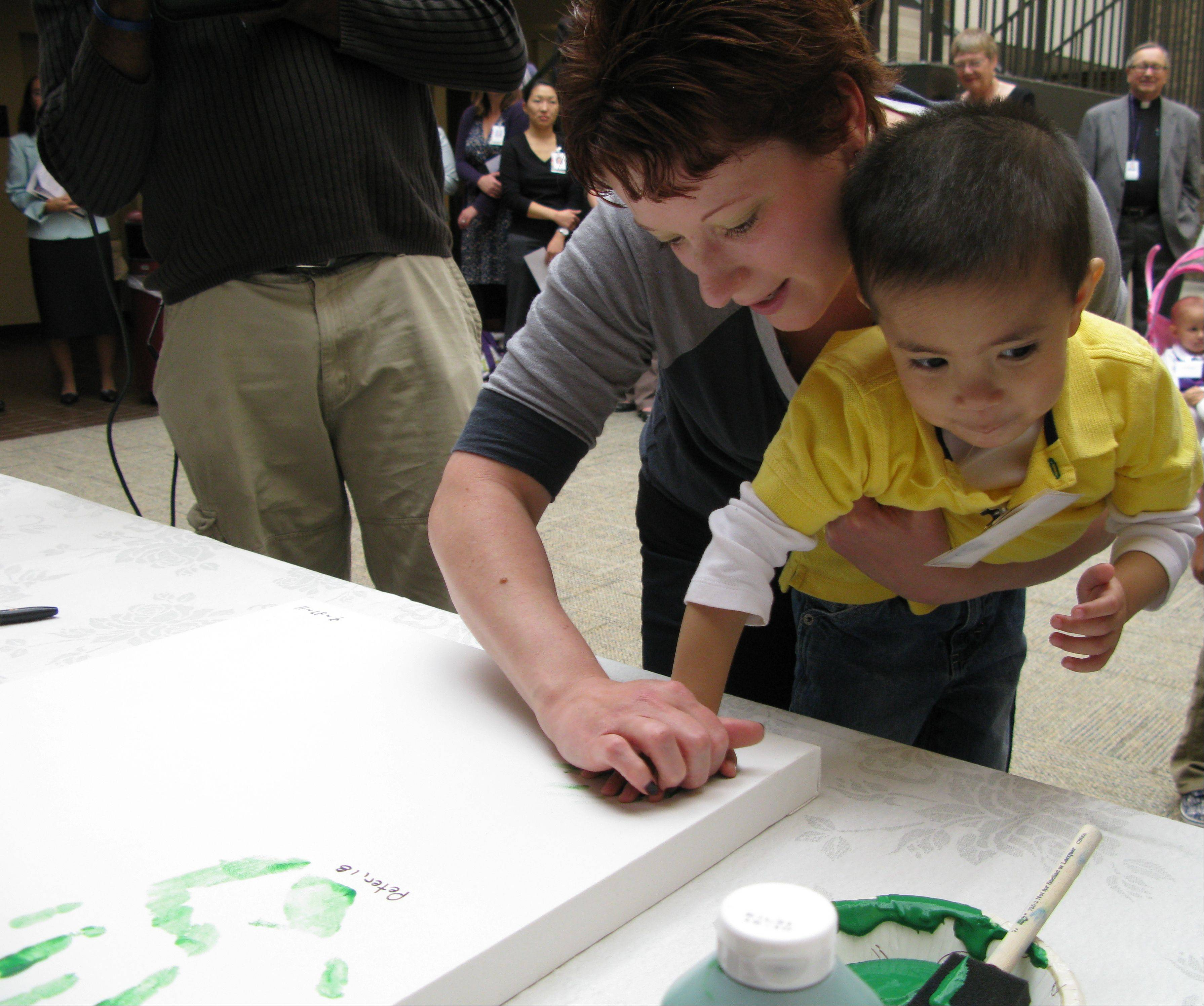 Cancer survivor Grayson Cacal, 2, of Chicago and his mother, Sara, make a hand imprint on a canvas that will grace a wall at Advocate Lutheran General Children's Hospital in Park Ridge, which Tuesday received a $100,000 grant to help fund its Pediatric Cancer Survivorship Program and clinic.