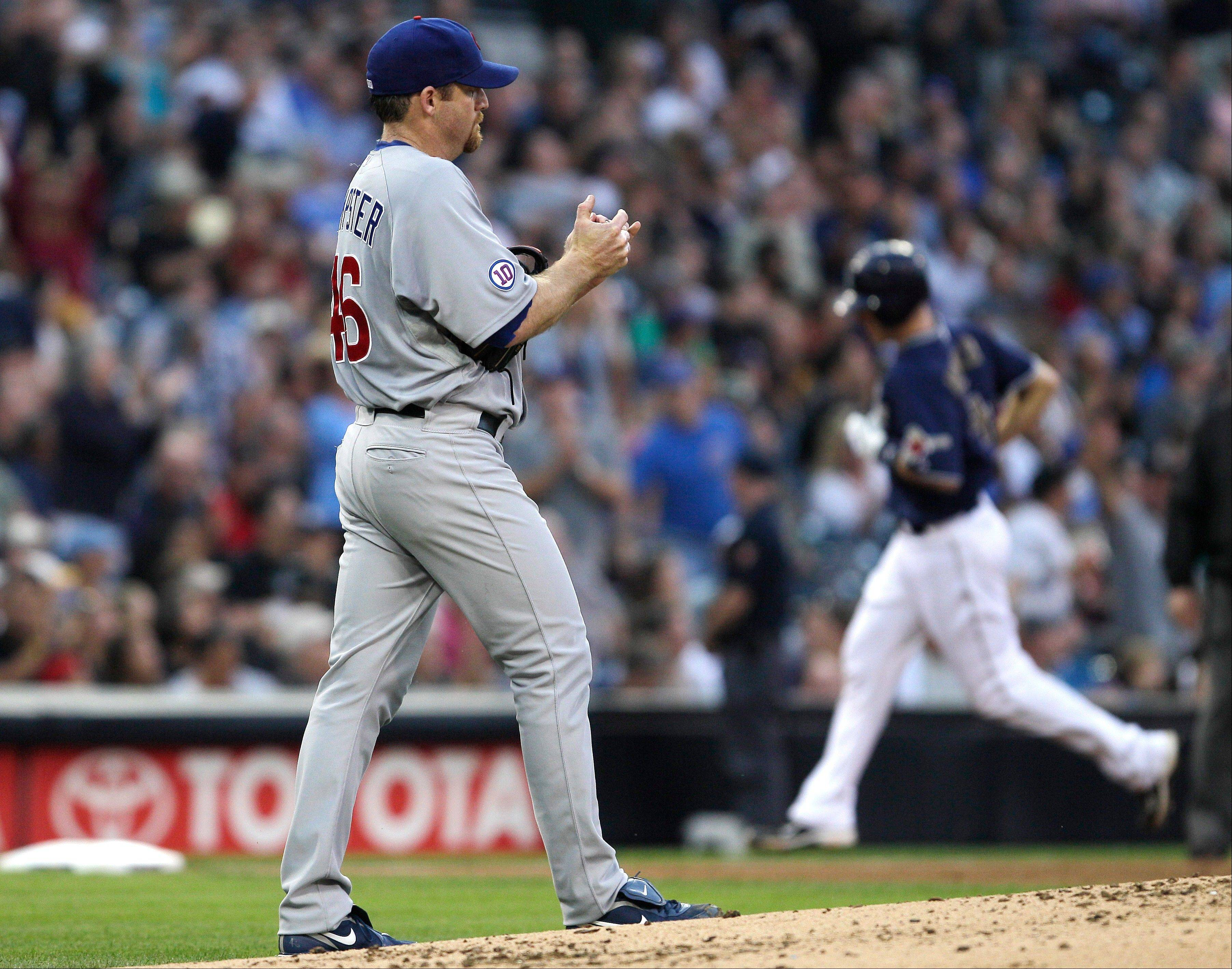 Chicago Cubs starting pitcher Ryan Dempster, left, rubs a new baseball as San Diego Padres' Nick Hundley rounds the bases with a three-run home run during the third inning of a game on Wednesday, Sept. 28, 2011, in San Diego.