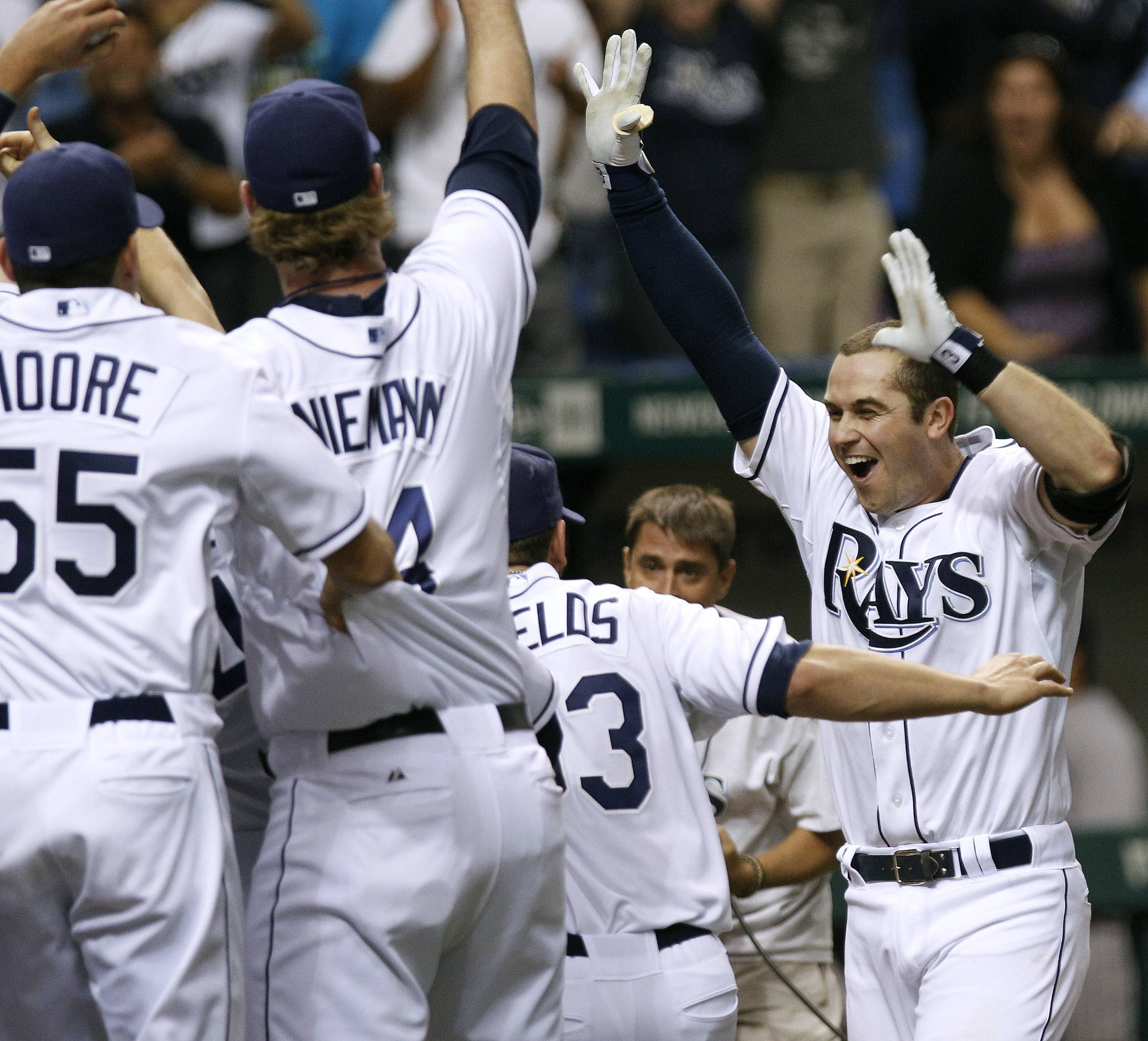 Evan Longoria, right, celebrates with teammates after his home run in the 12th inning against the New York Yankees. The Rays defeated the Yankees 8-7 and won the AL wild card.