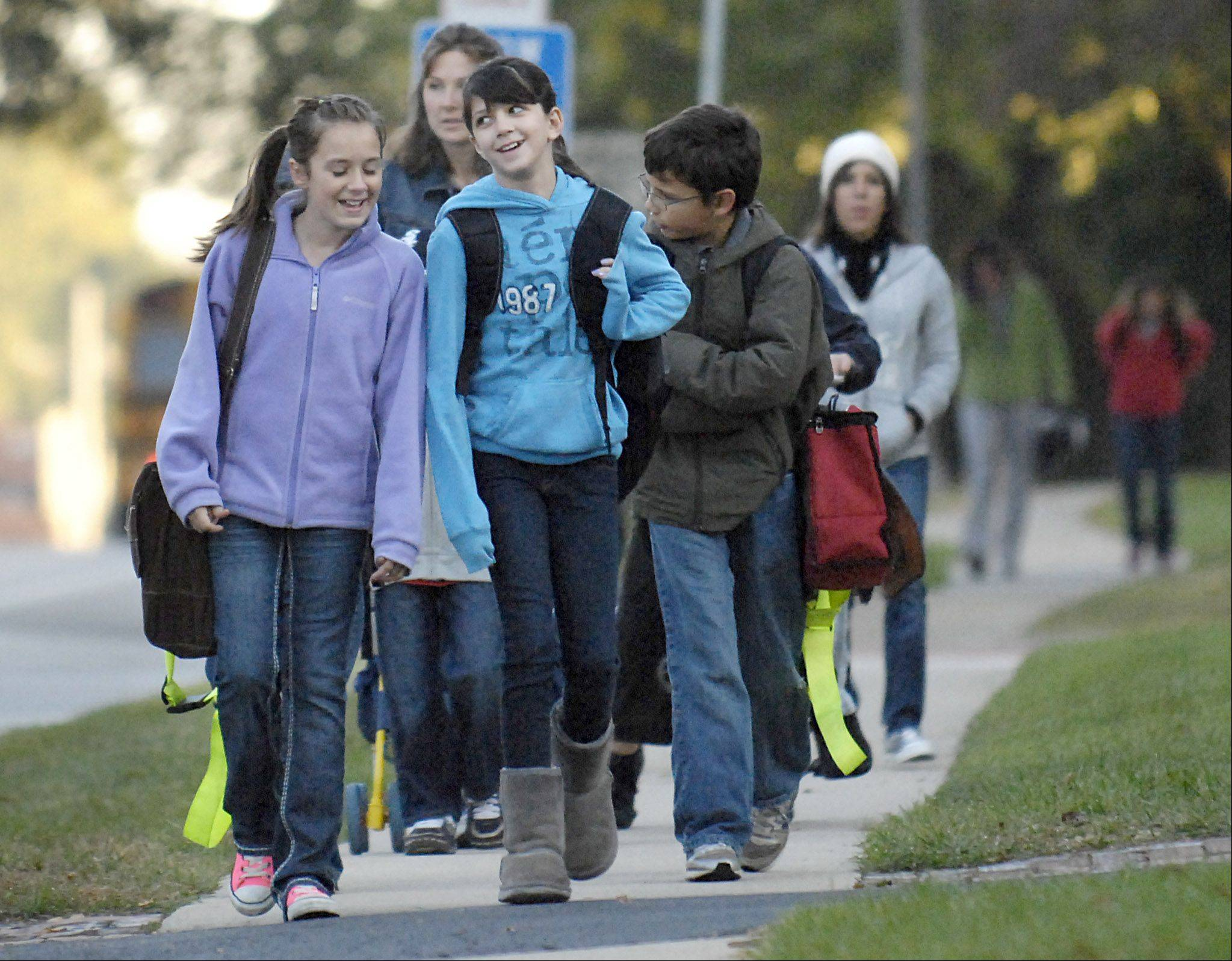 Harrison Elementary fifth-graders Olivia Tegge, left, and Holly Friedel, both 10, walk down East Side Drive in Geneva on their way to school on International Walk to School Day last year. This year's event is set for Wednesday, Oct. 5, throughout Kane County.