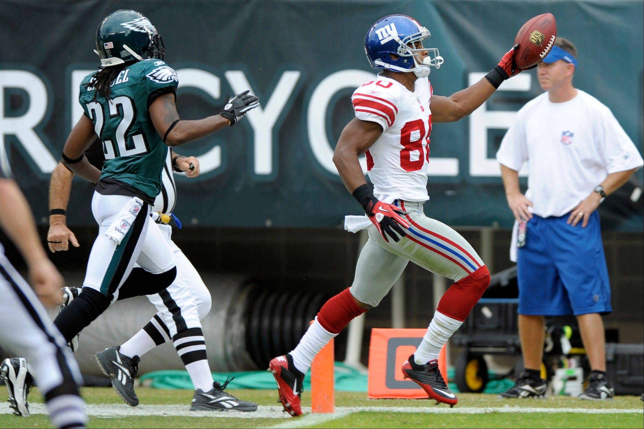 New York Giants wide receiver Victor Cruzscores a touchdown with Philadelphia Eagles cornerback Asante Samuel in pursuit Sunday in Philadelphia. Over two games, Matt Ryan and Eli Manning have burned the Eagles defense for 4 touchdowns apiece.