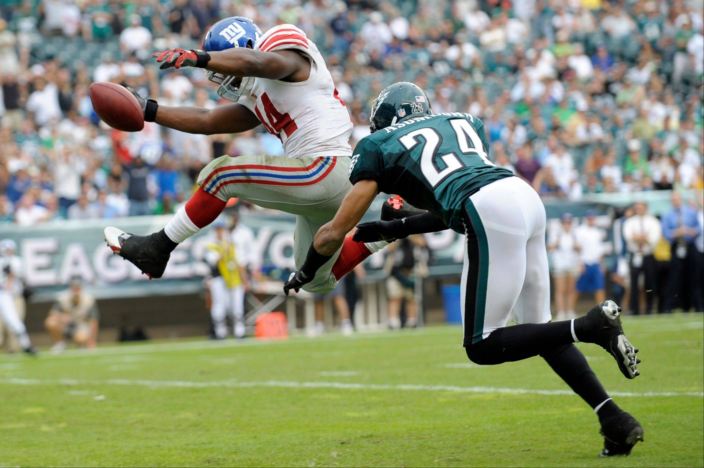 New York Giants running back Ahmad Bradshaw leaps into the end zone for a touchdown as Philadelphia cornerback Nnamdi Asomugha arrives to late Sunday in Philadelphia.