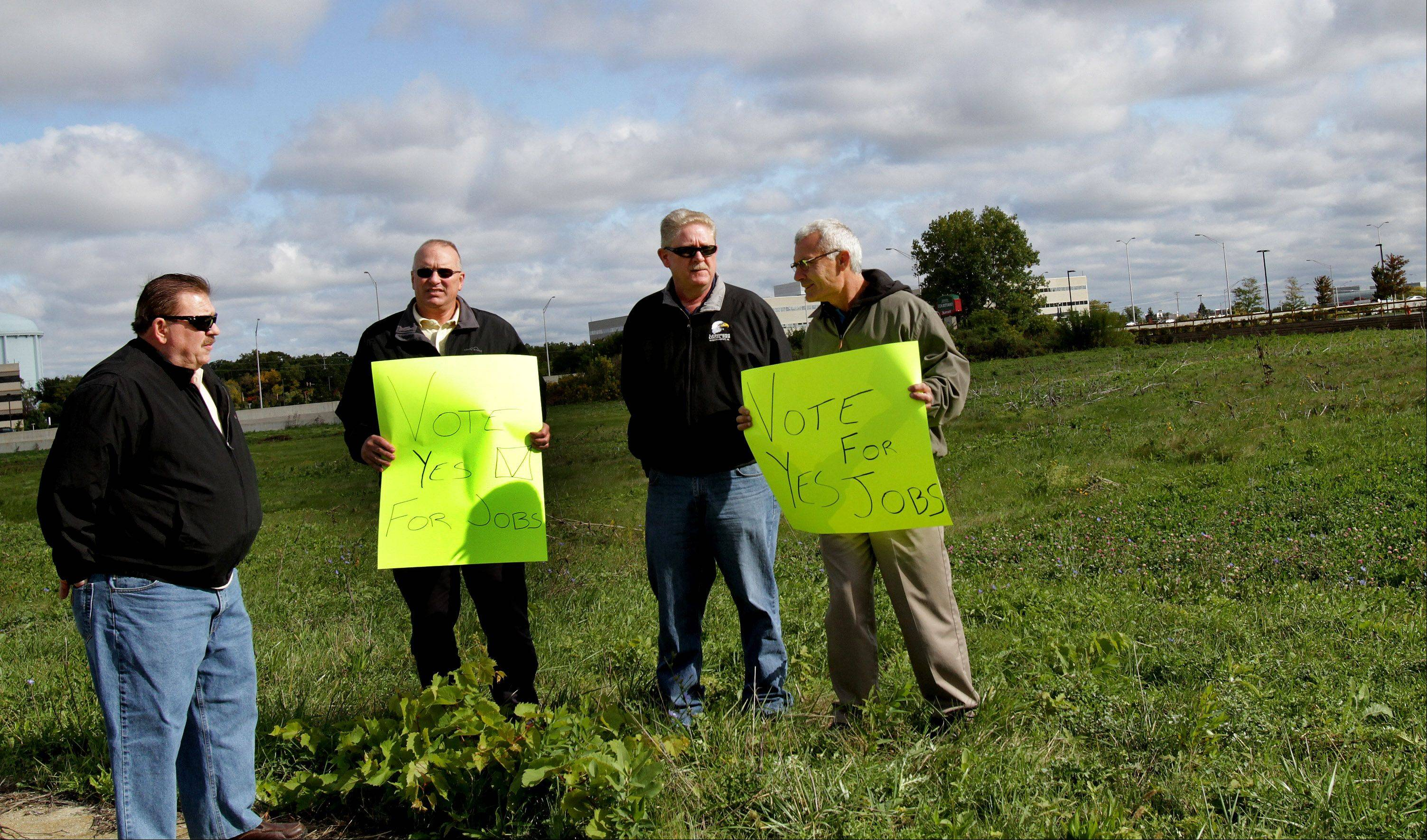 Four union members gathered Friday in Naperville to show support for the proposed Freedom Plaza Development.