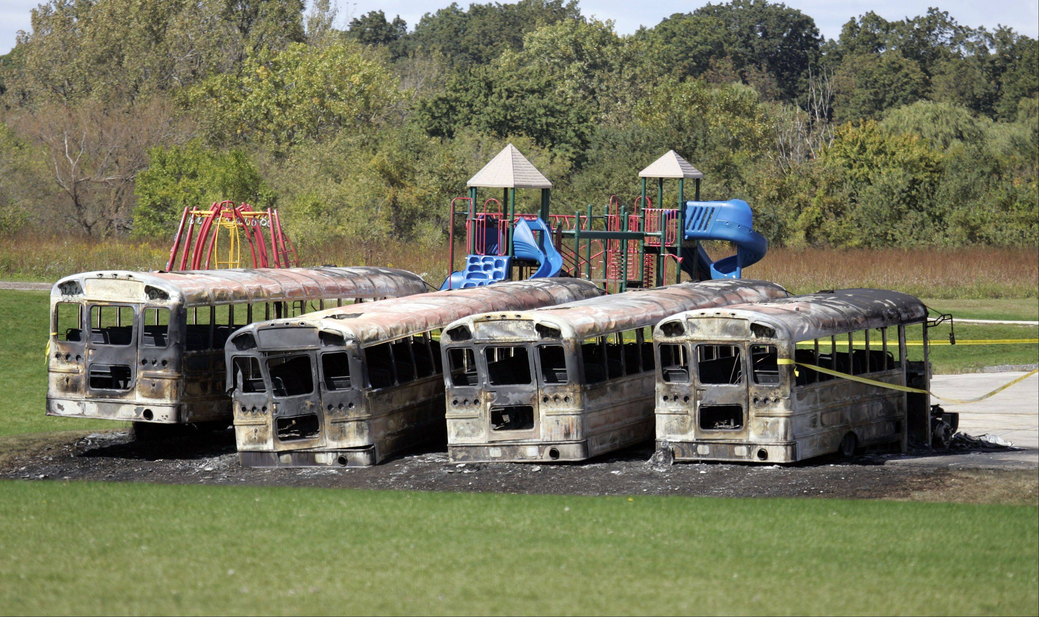 Buses destroyed by fire sit in the parking lot Friday afternoon at Prairie View Grade School, 10N630 Nesler Road, Elgin.