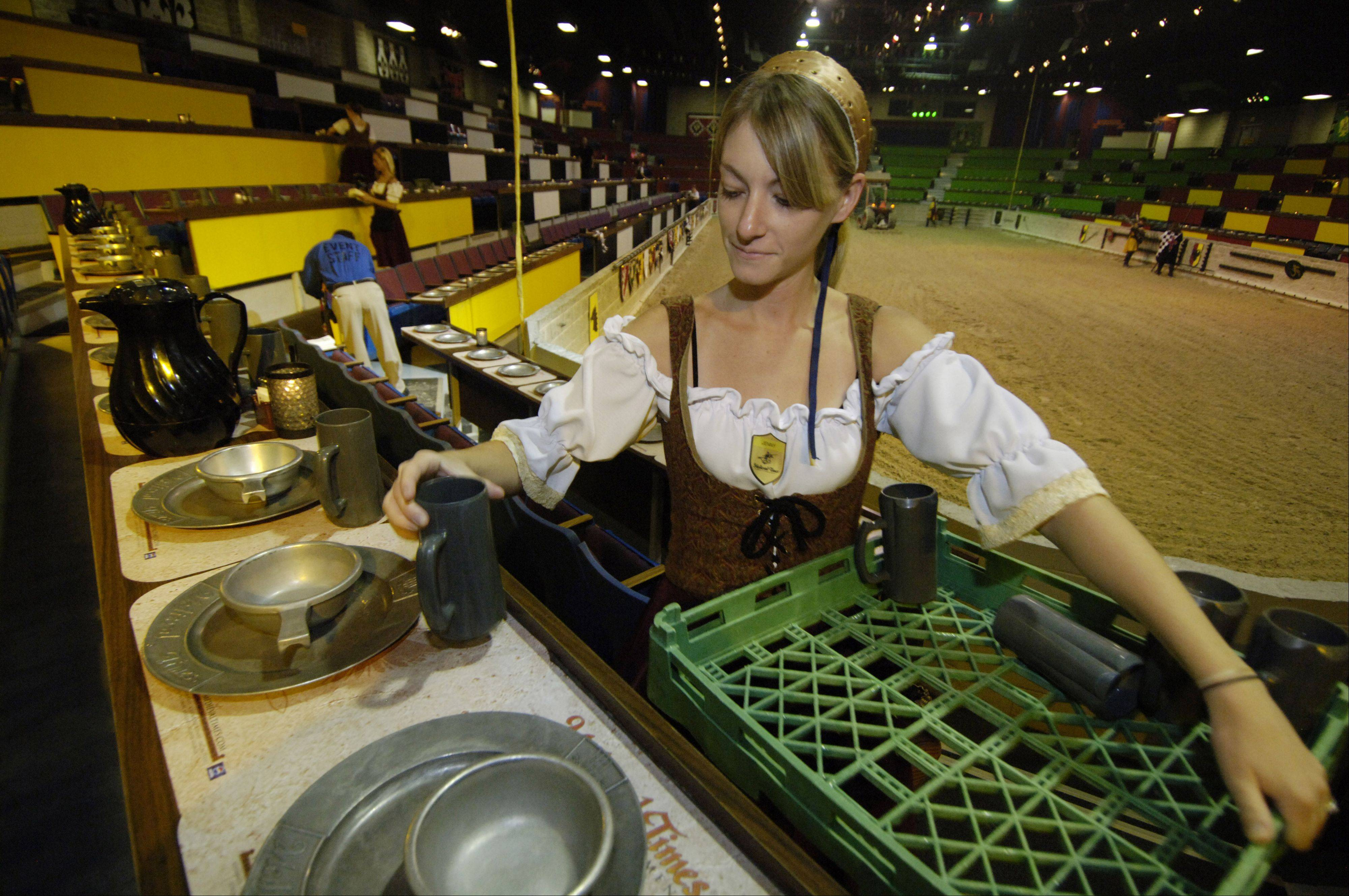 Jenny Nolan places a mug with a table setting before the show at Medieval Times.