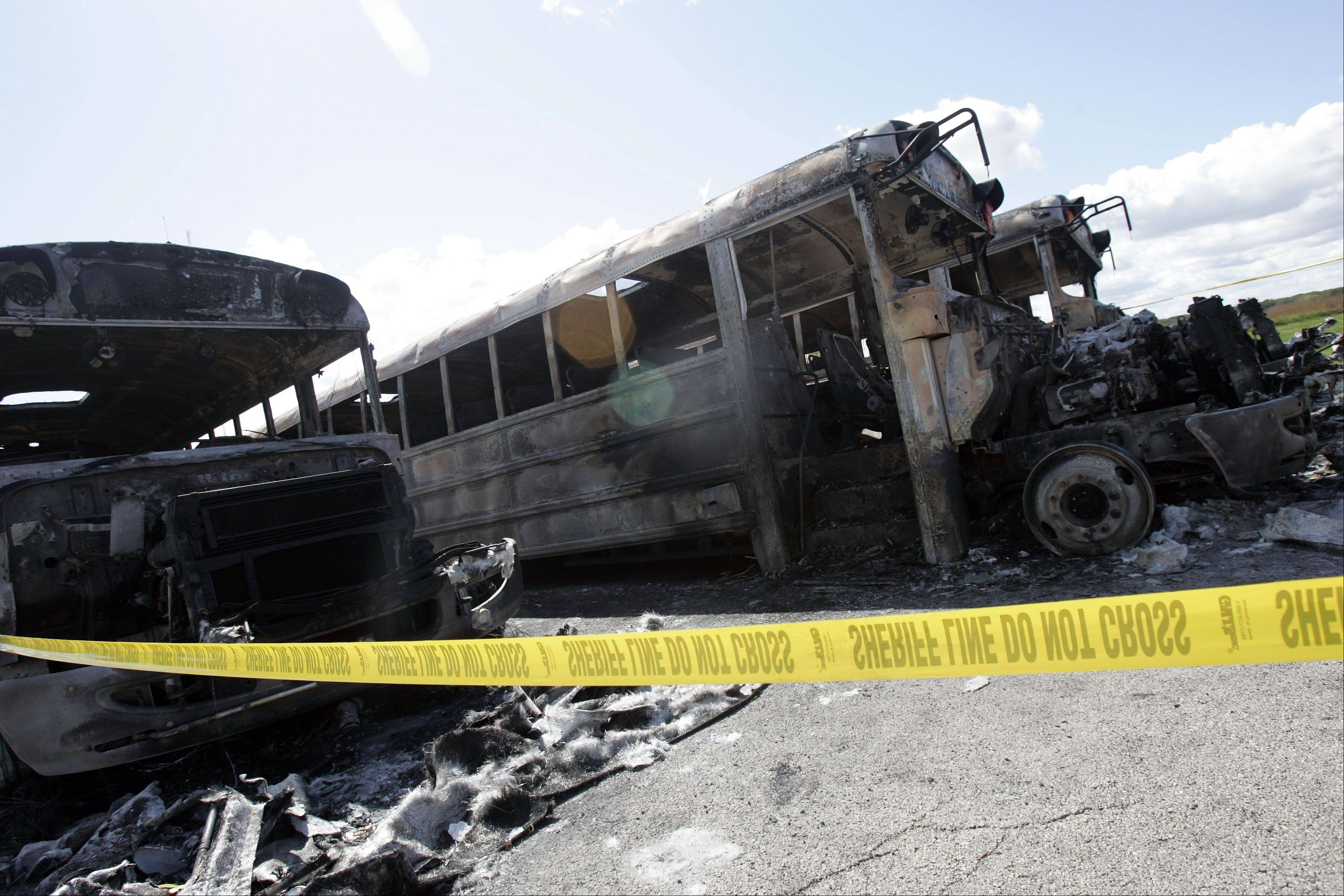 Brian Hill/bhill@dailyherald.comBuses destroyed by fire sit in the parking lot Friday afternoon at Prairie View Grade School near Elgin.