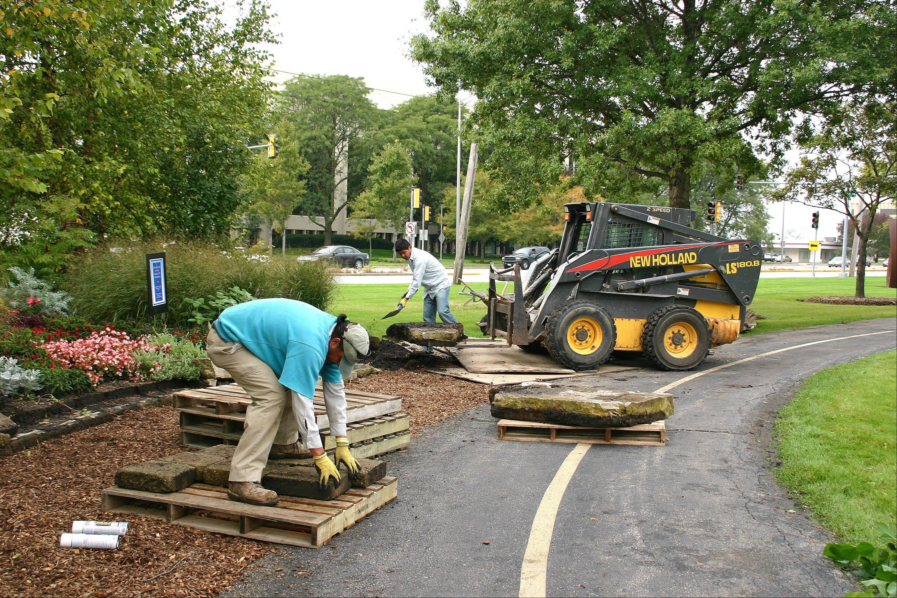 Existing planter wall stones are removed Thursday at Lake Park to make way for the Flight 191 Memorial that will be unveiled on Oct. 15.