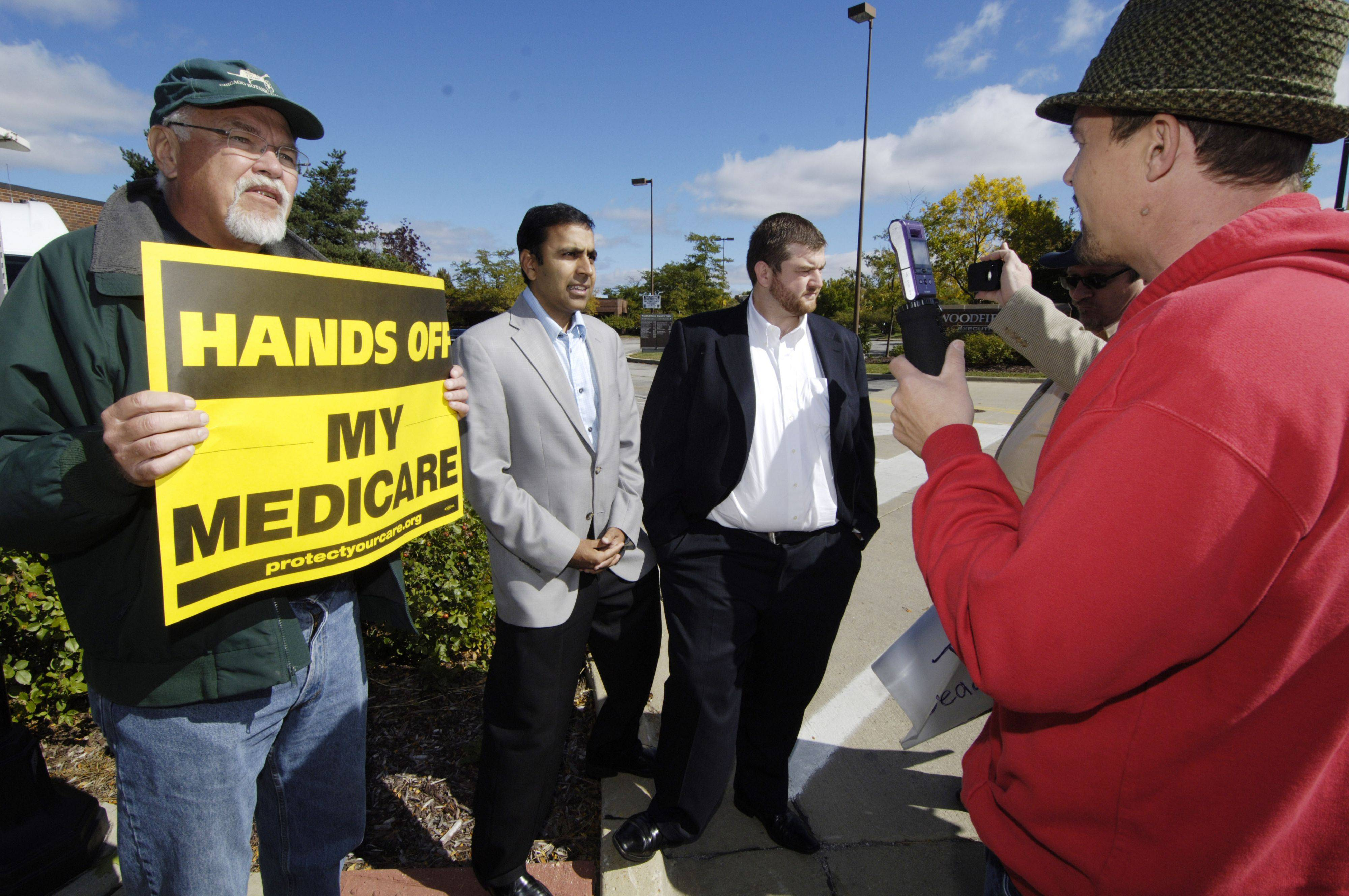 TeaCon supporter Adam Sharp, right, of St. Louis confronts counter-protester Alan Prochaska of Hoffman Estates as well as congressional candidate Raja Krishnamoorthi and his campaign spokesman Mike Murray, with a video camera in hand outside the Midwest Tea Party Convention, at the Renaissance Hotel in Schaumburg Saturday.