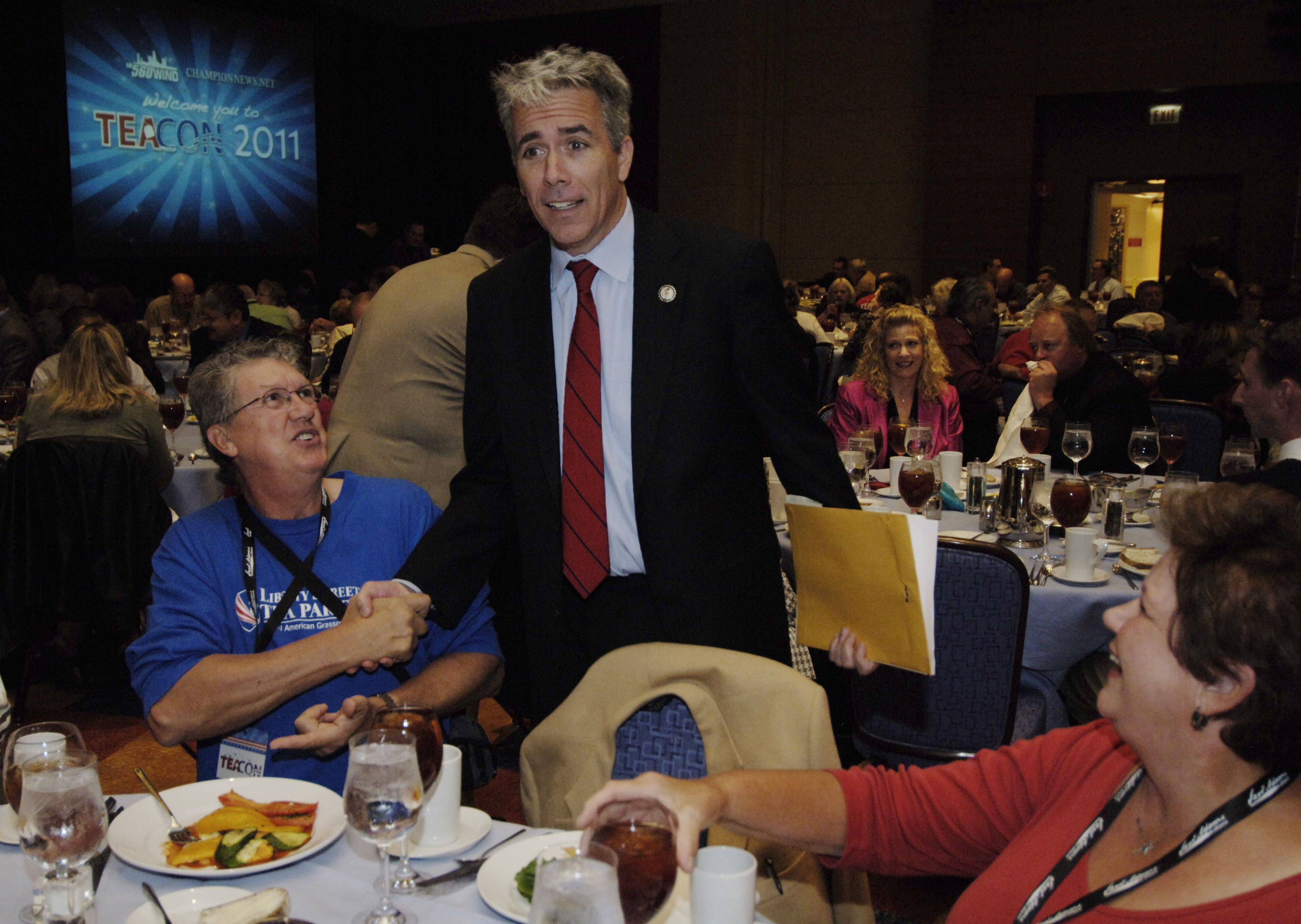 Congressman Joe Walsh is greeted by supporters, including Glen Rowe, left, of Wauconda, during TeaCon, the Midwest Tea Party Convention, at the Renaissance Hotel in Schaumburg Saturday.
