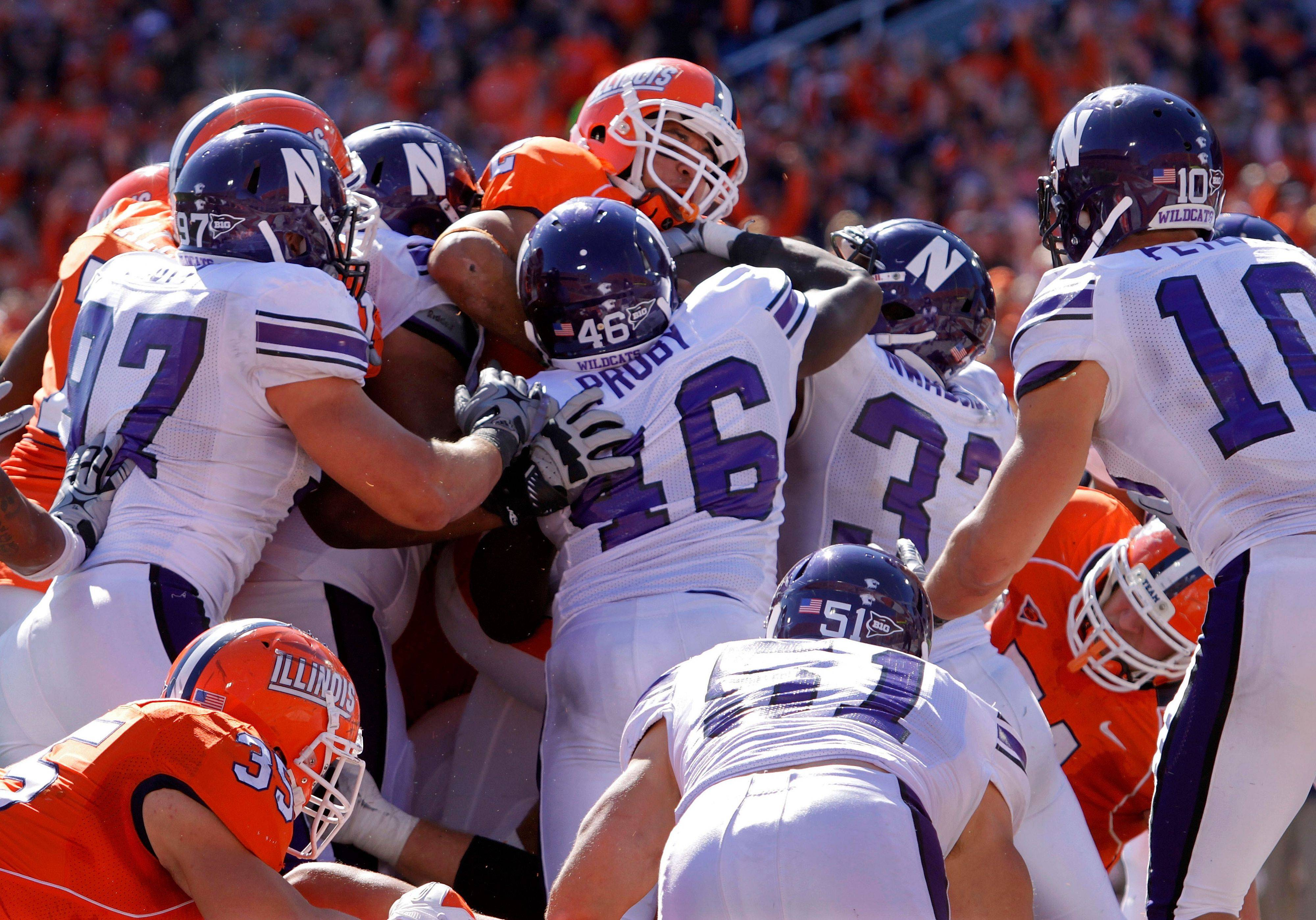 Illinois quarterback Nathan Scheelhaase, top, pushes through the Northwestern defense to score the game-winning touchdown in the closing seconds Saturday.