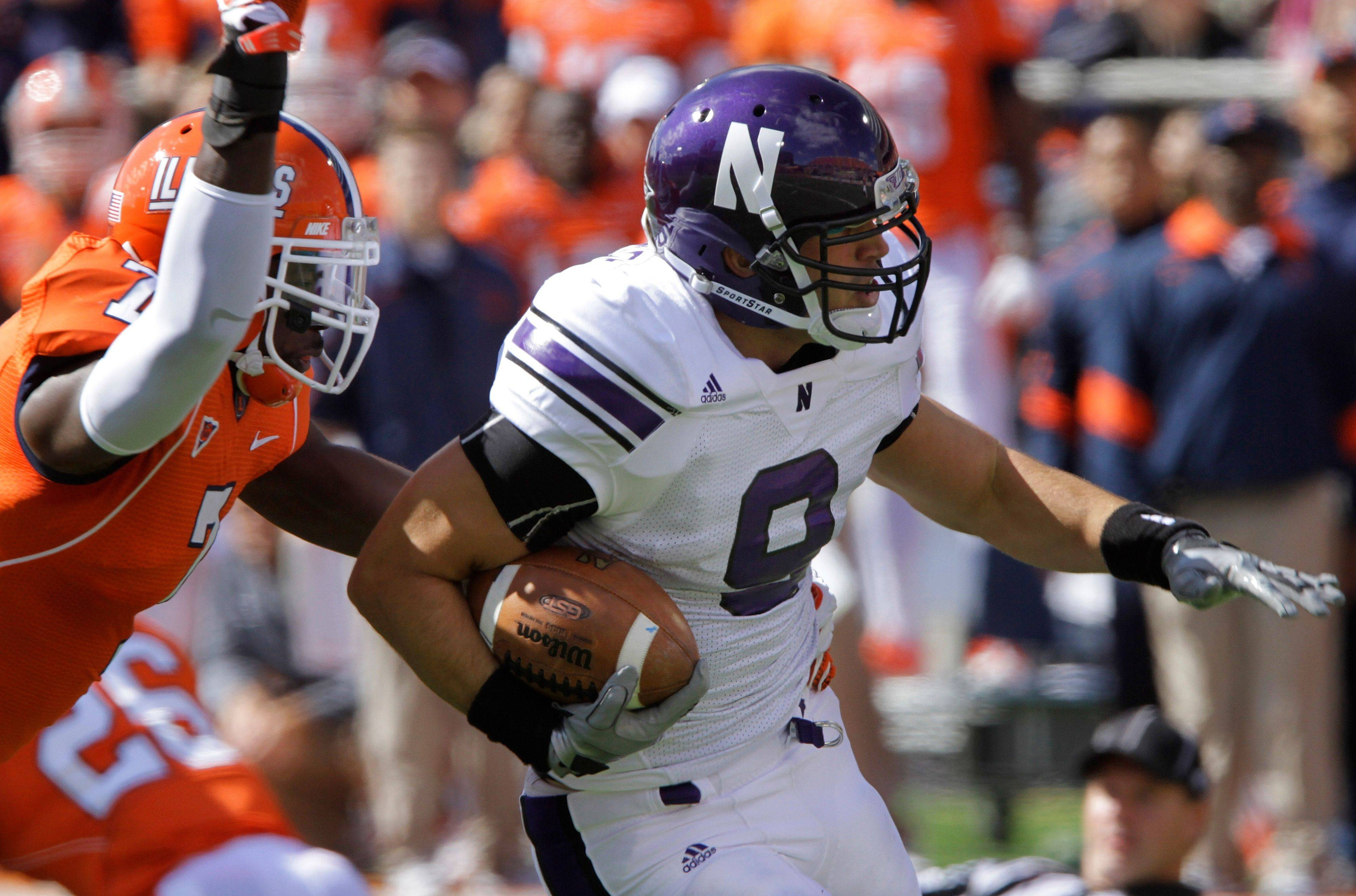 Northwestern tight end Drake Dunsmore holds onto a pass as Illinois defensive back Supo Sanni defends during the first half Saturday in Champaign.