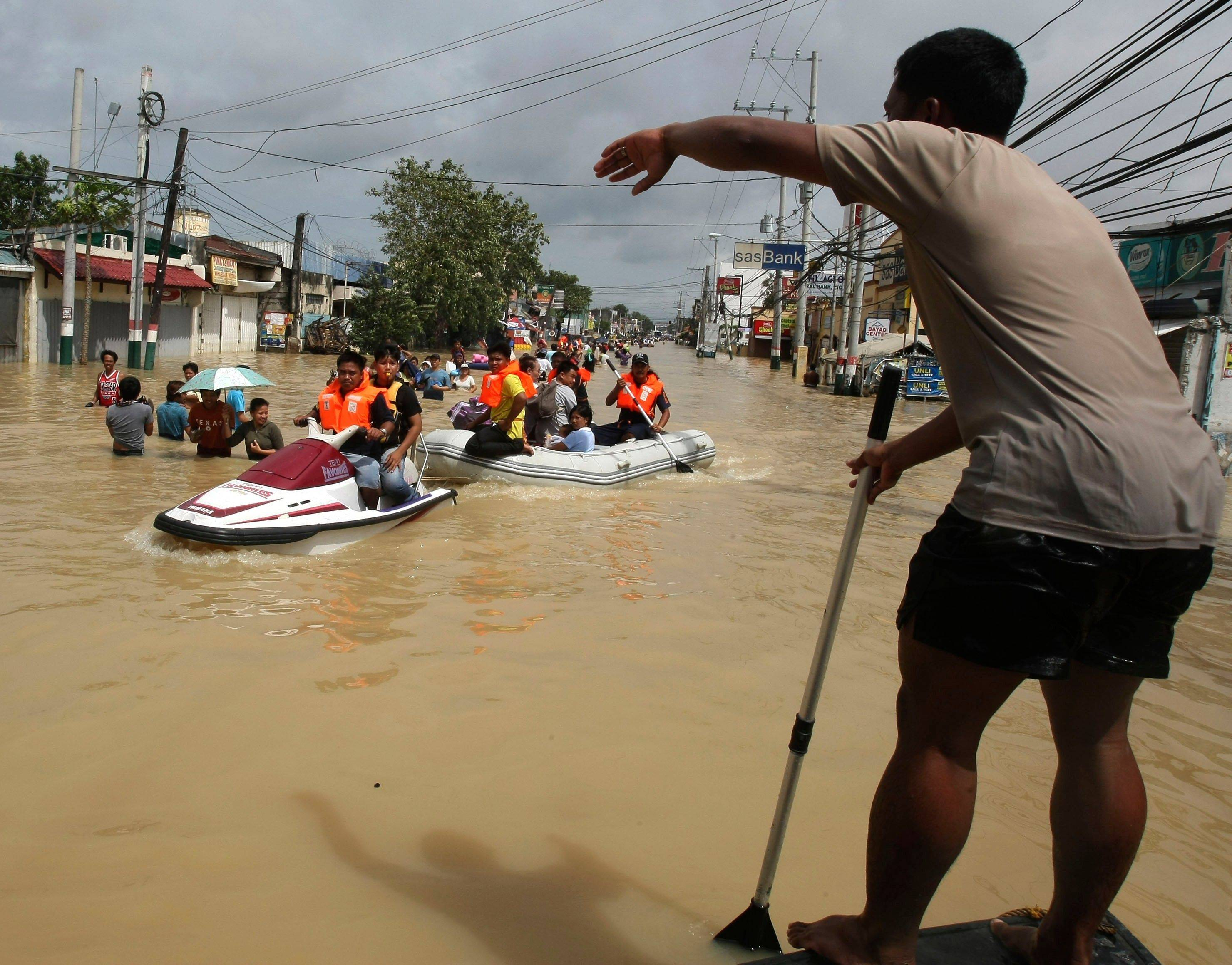 A Philippine Navy Officer Guides Rescuers As Flooding Continues For The Fourth Day Sunday Oct
